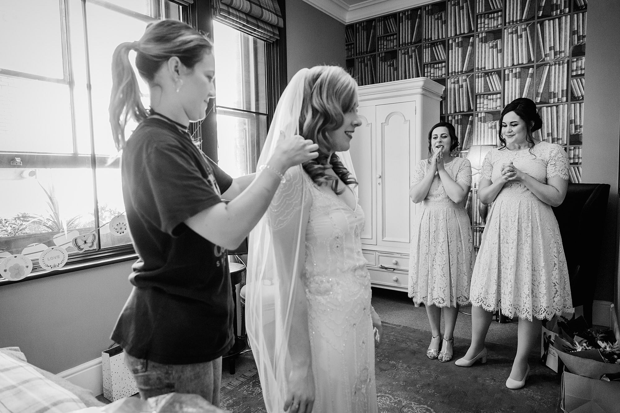 bridesmaids watch as bride's veil is put in
