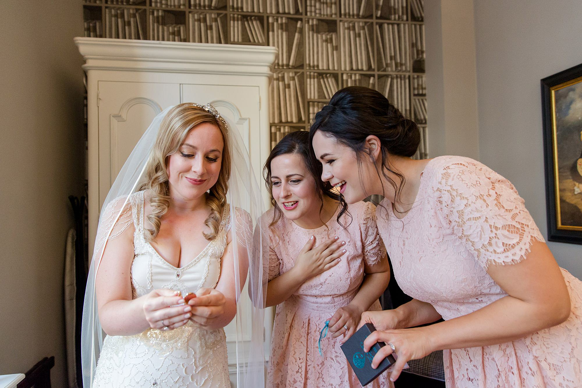 bride shows bridesmaids her gift from groom