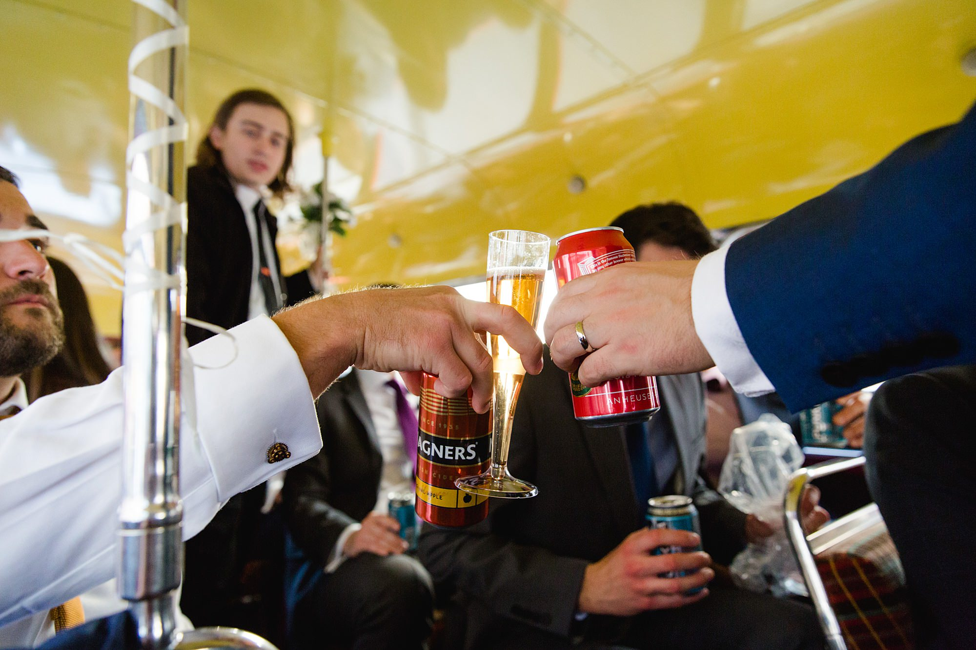 guests make a toast on wedding bus