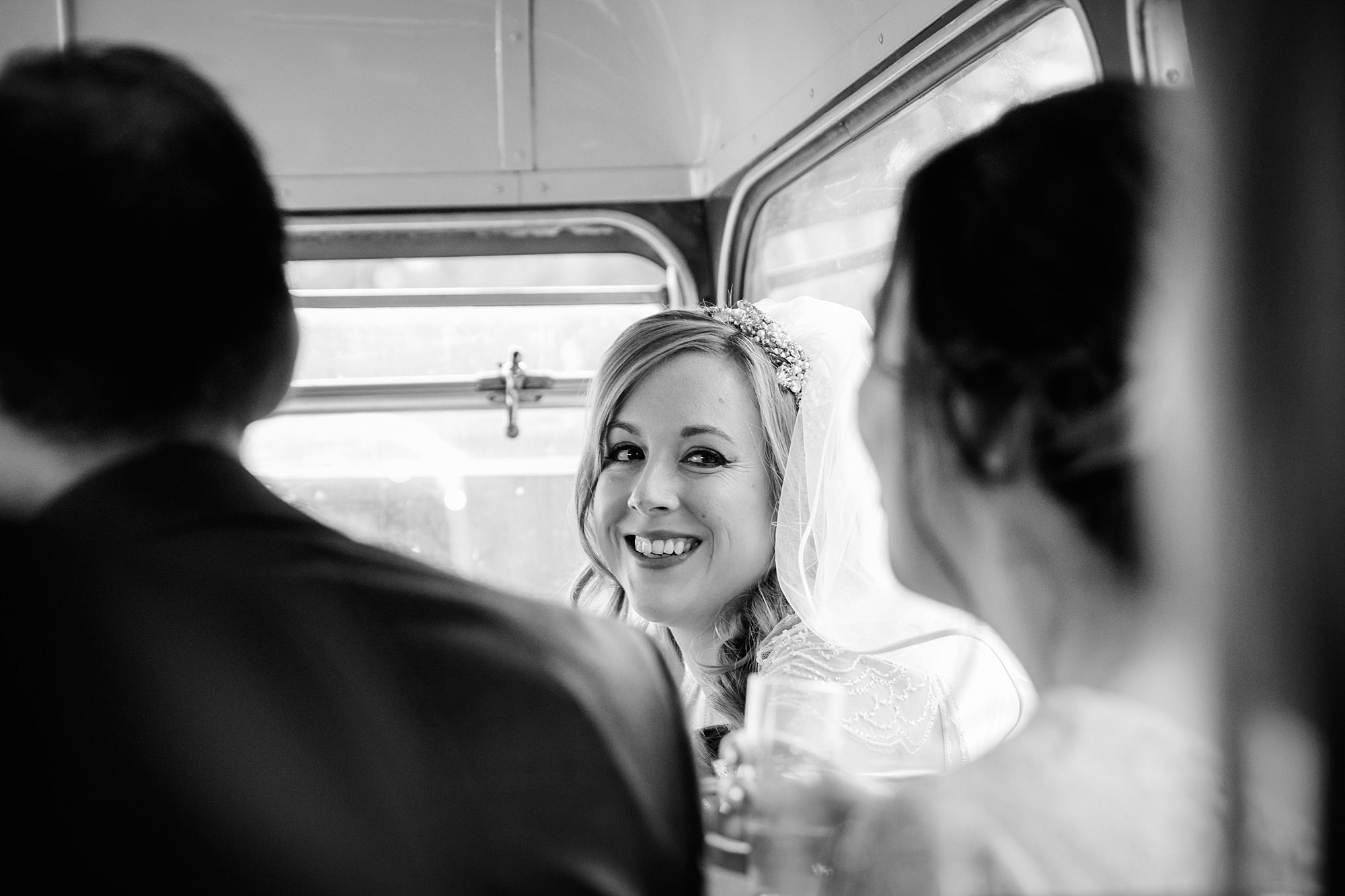 bride chats to guests on bus to Harrild and sons wedding