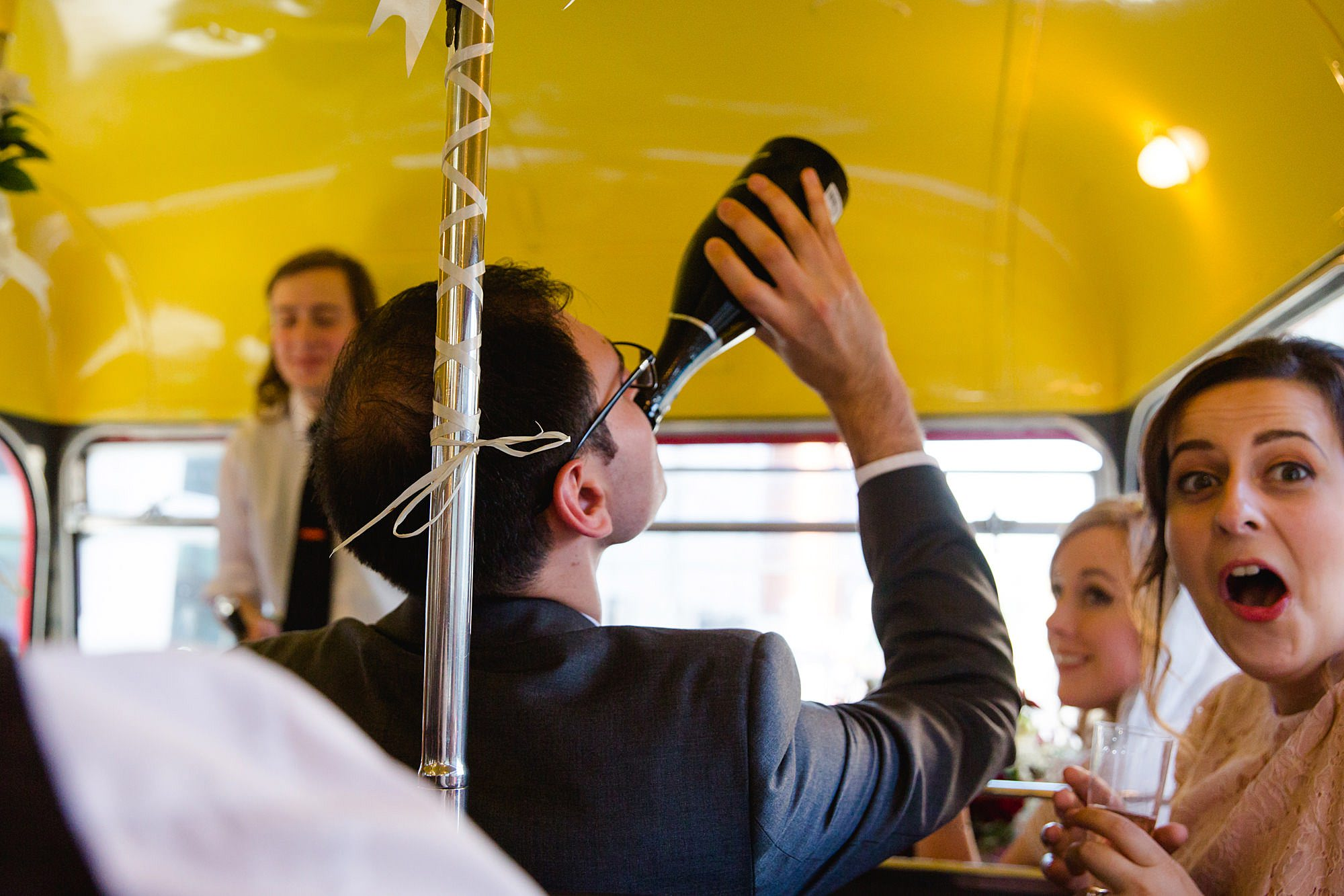 guests swigs from change bottle on bus