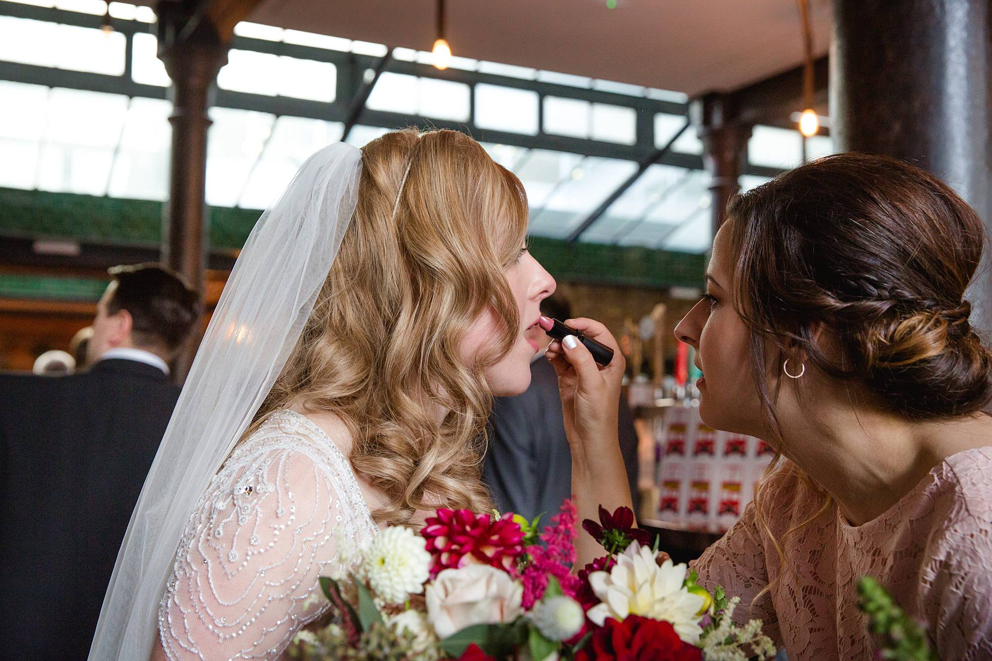 Harrild and sons wedding bridesmaid applies lipstick on bride