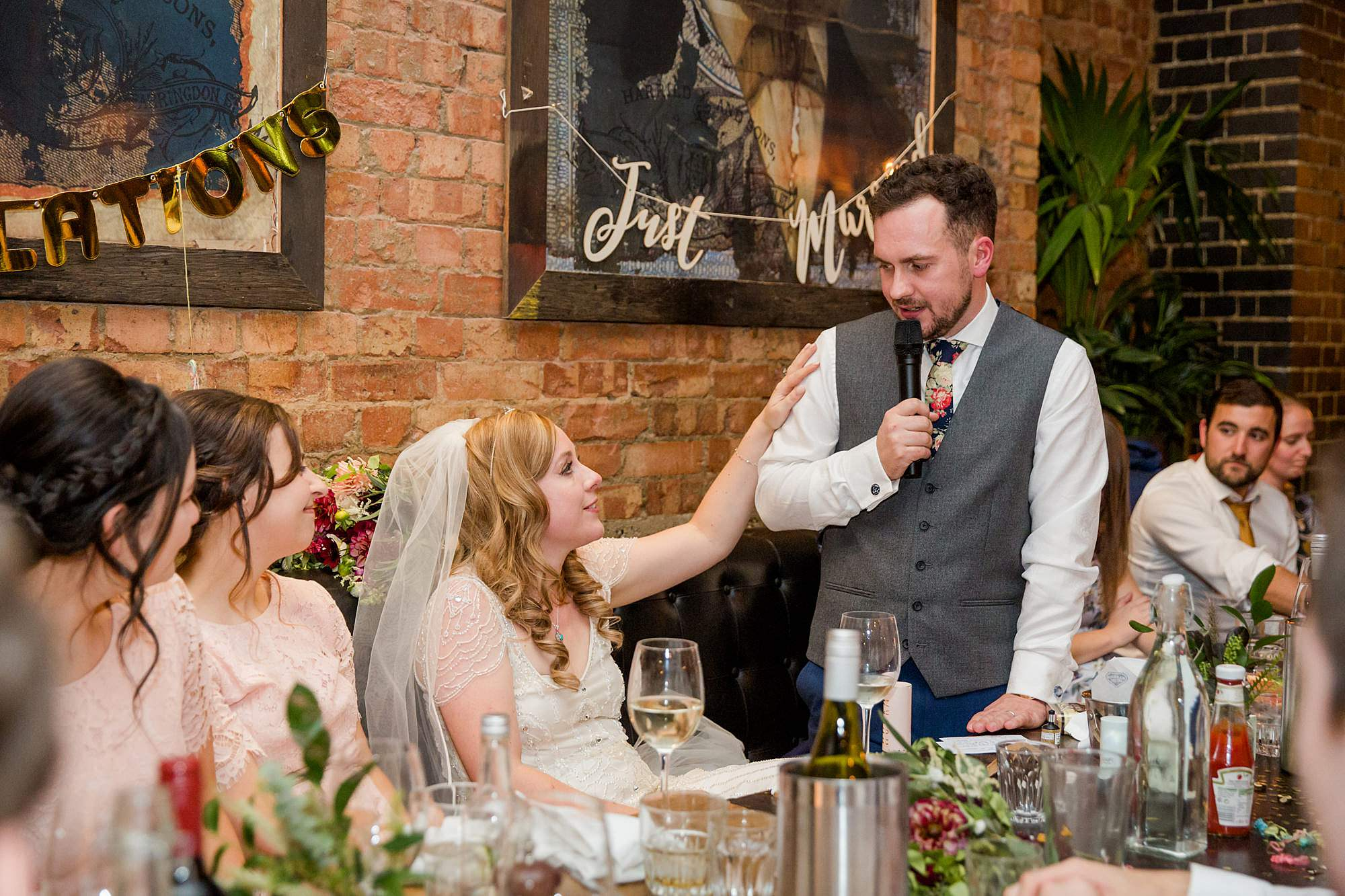 bride comforts groom during speech at Harrild and sons wedding
