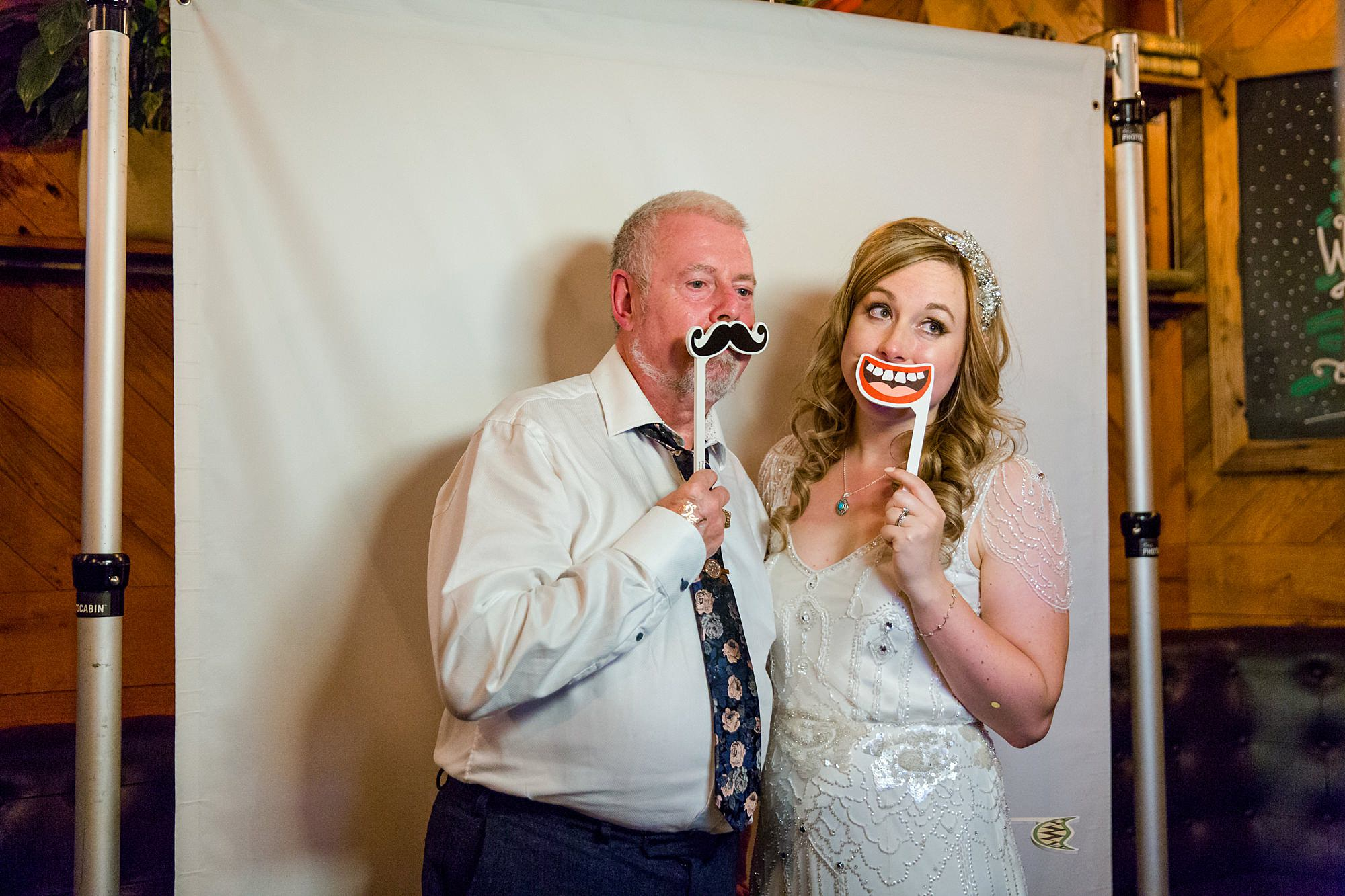 bride and guest with funny photo props