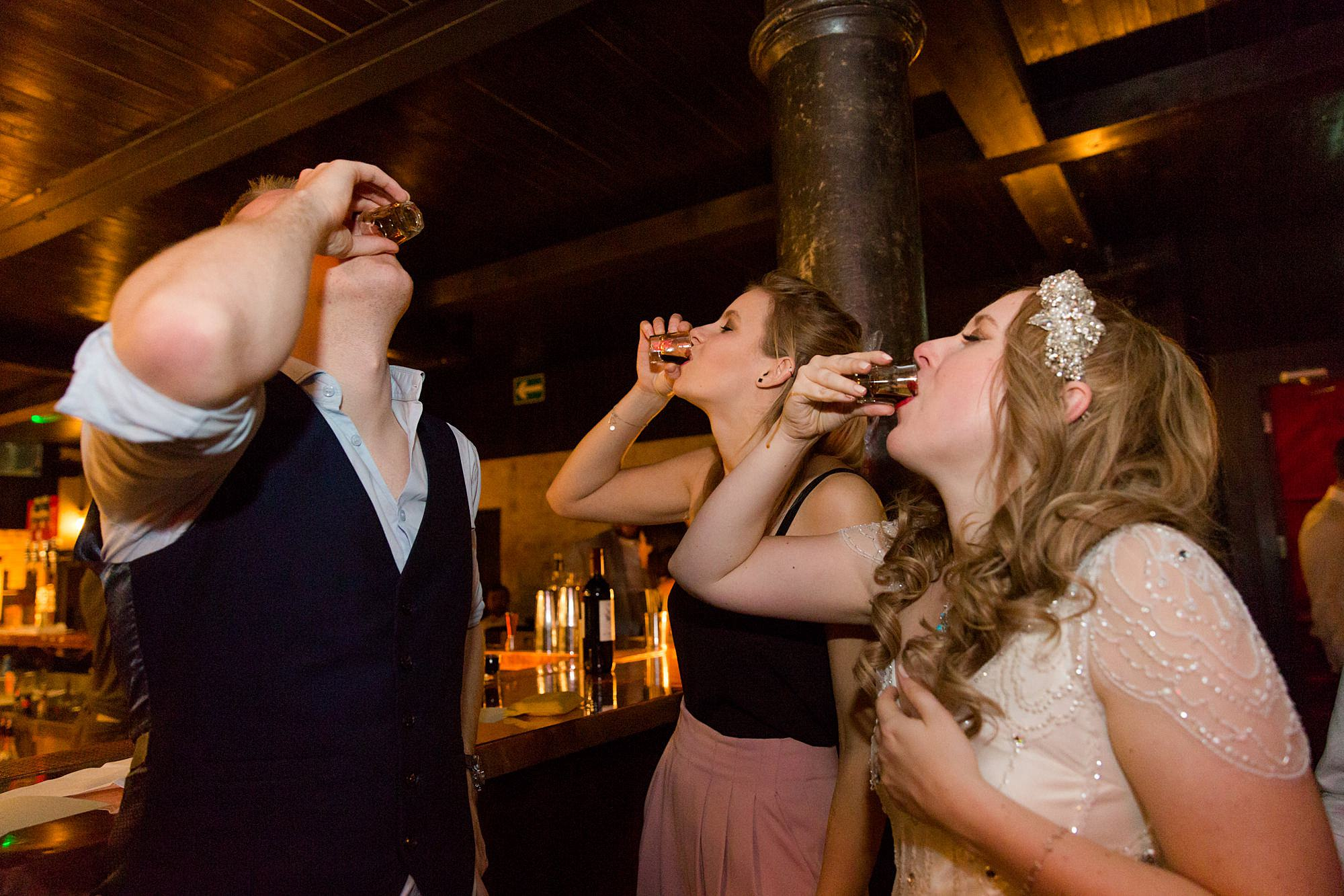 bride and guests take a shot