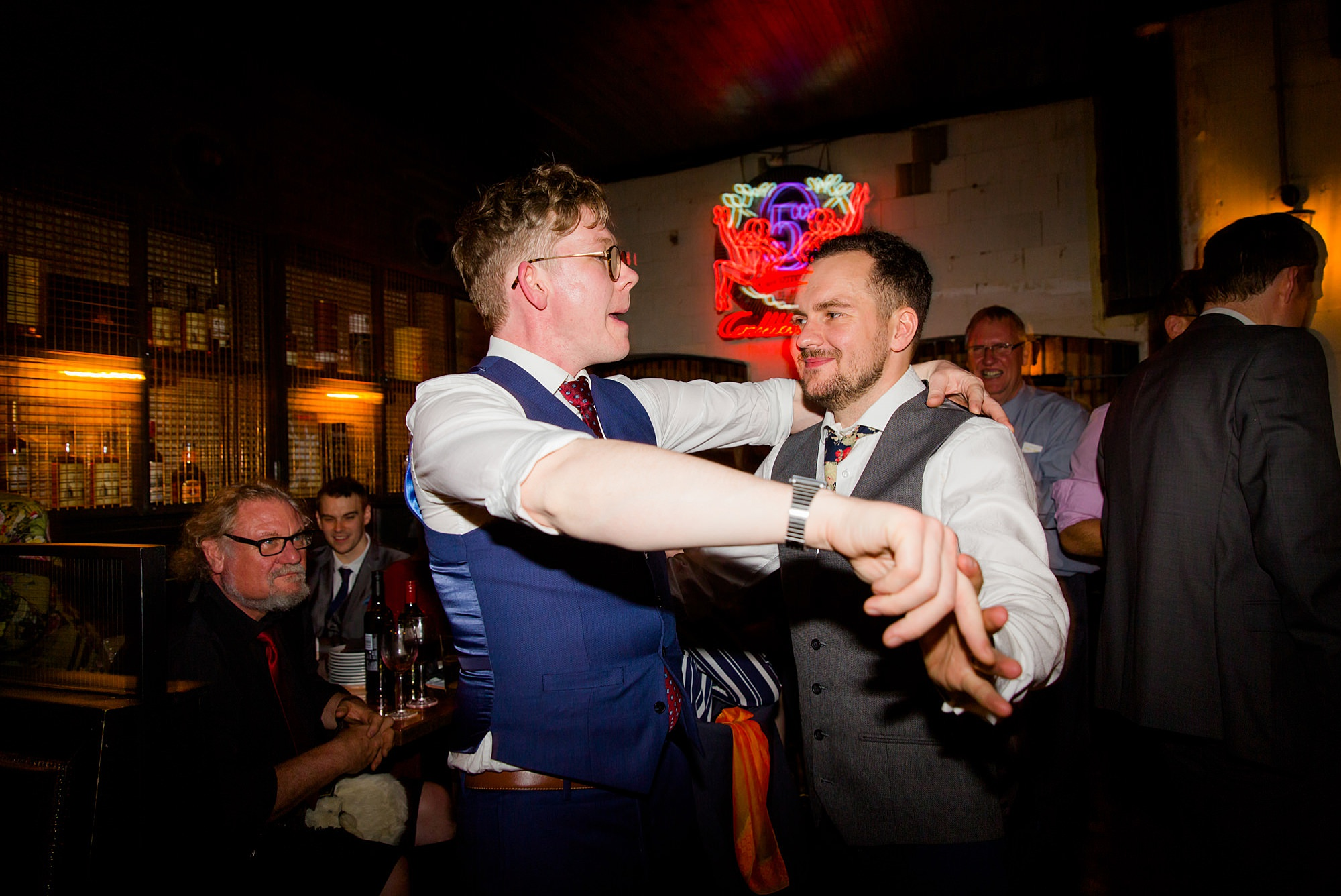 a groom dances with his friend