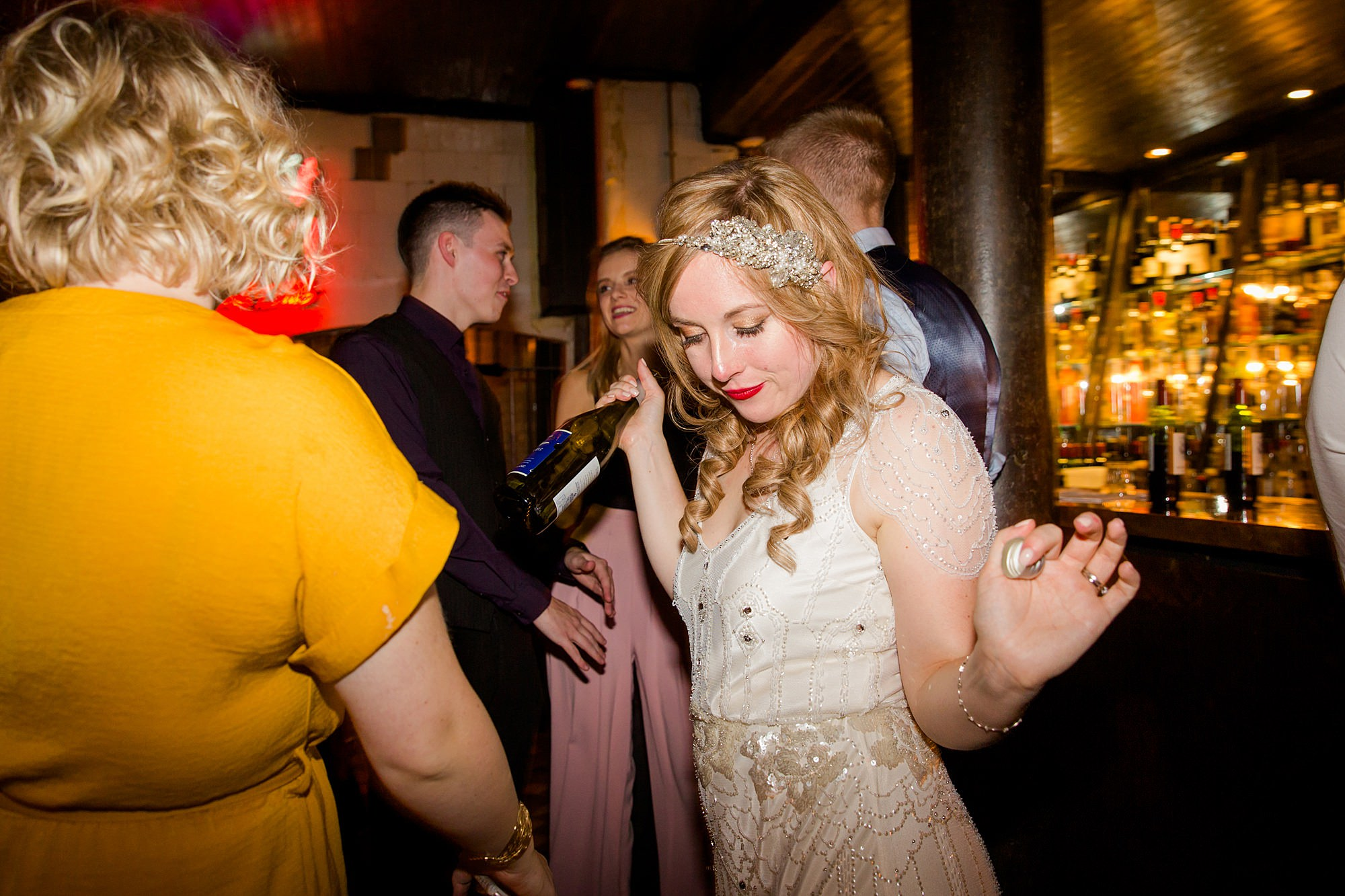 bride on dance floor with champagne bottle