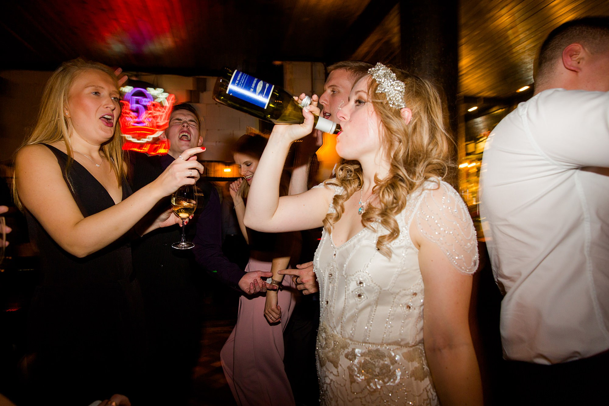 bride drinking champagne from bottle