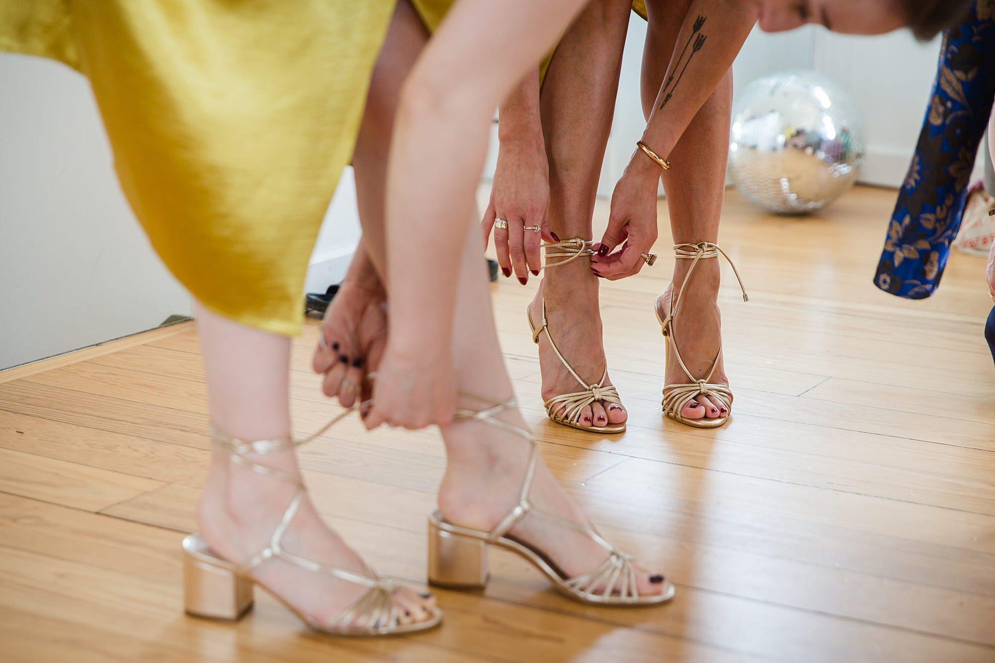 bridesmaids tying sold shoe straps