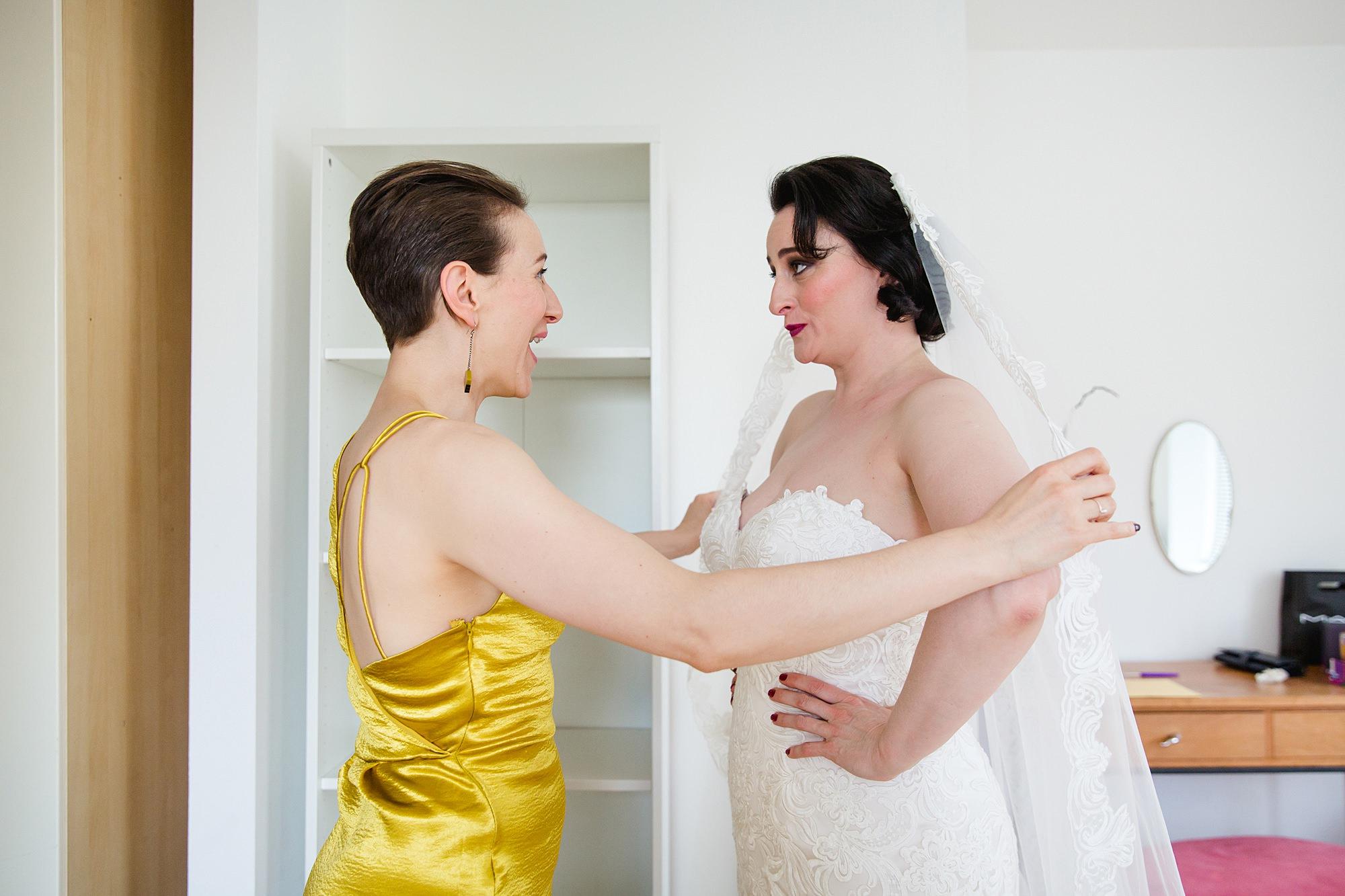 bridesmaid helps bride with veil