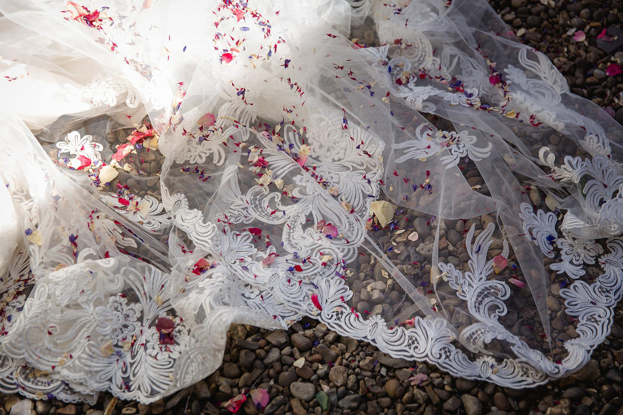 close up detail of bride's wedding dress with confetti