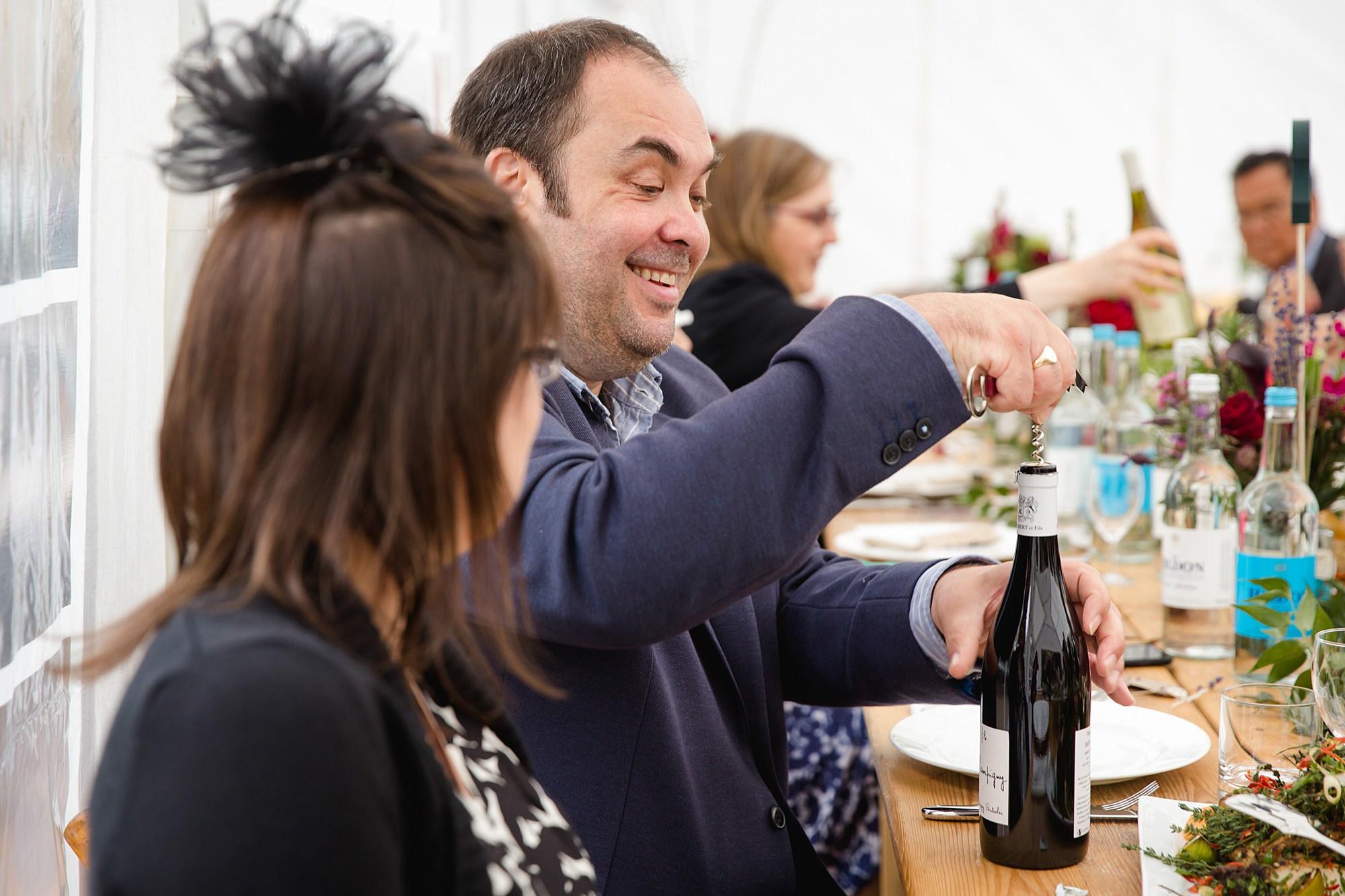 wedding guest opening bottle of wine
