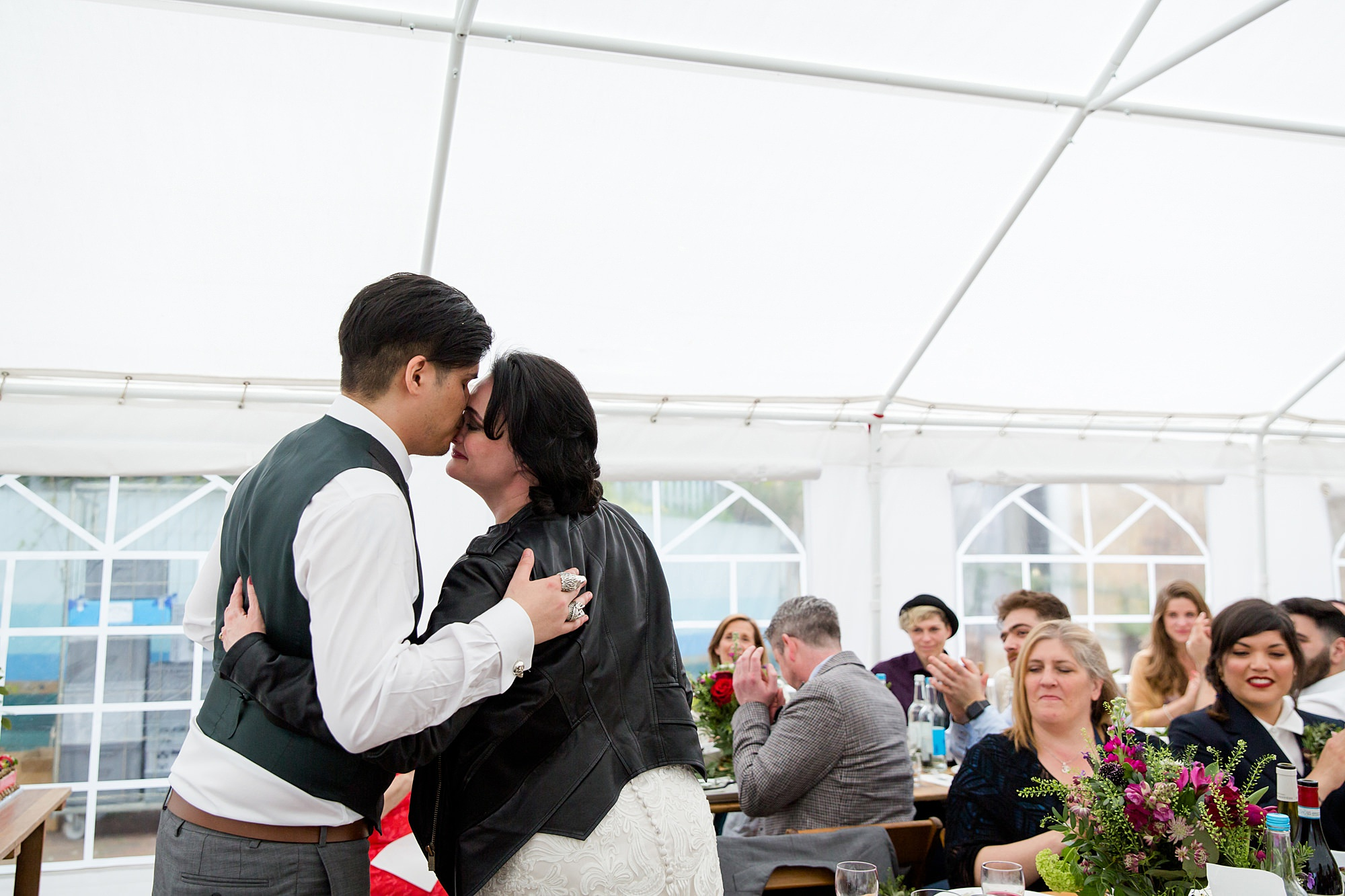 bride and groom kiss during speeches