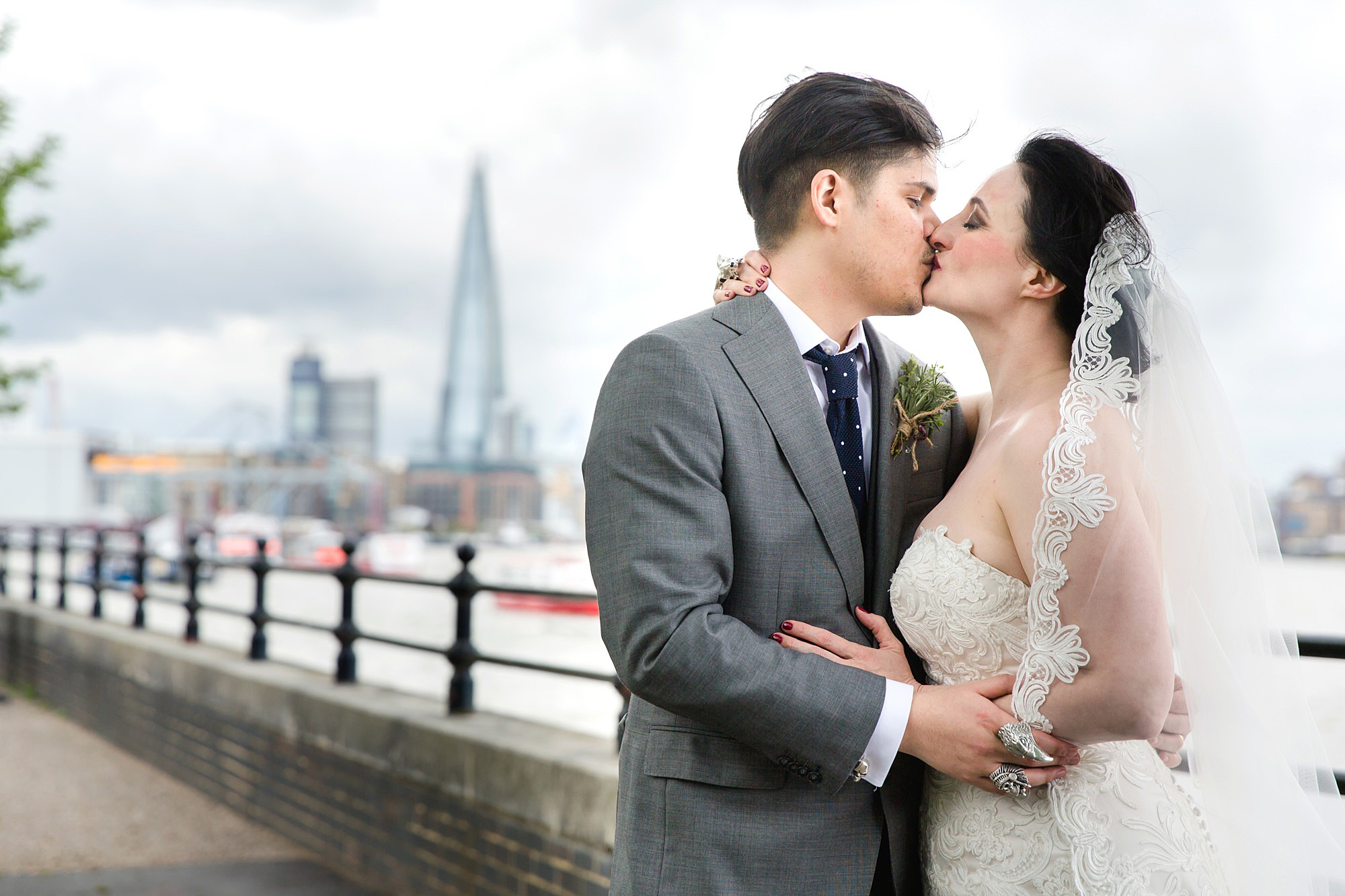 bride and groom kiss on Thames riverside