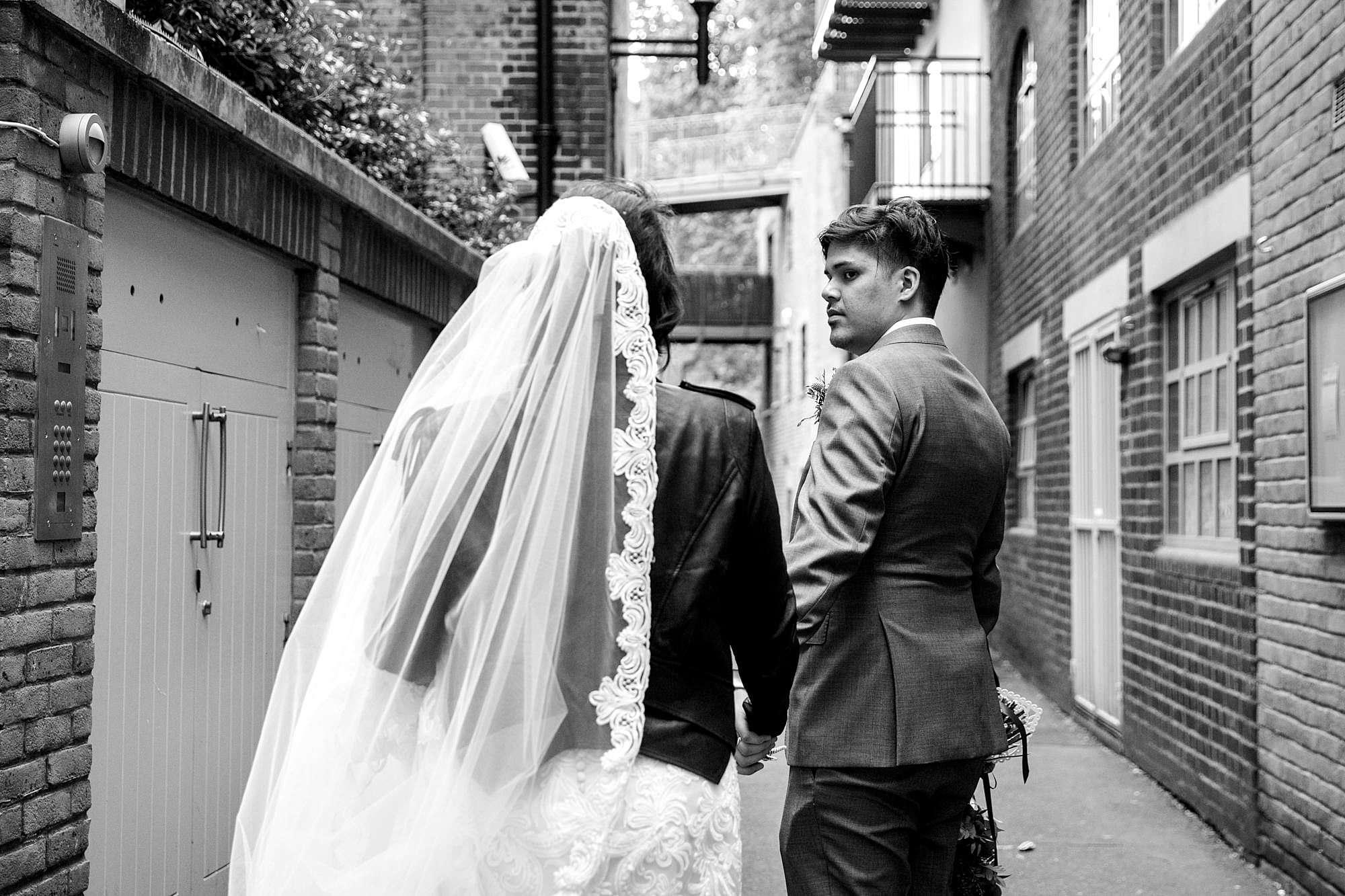 Brunel museum wedding bride and groom walking through alleyway
