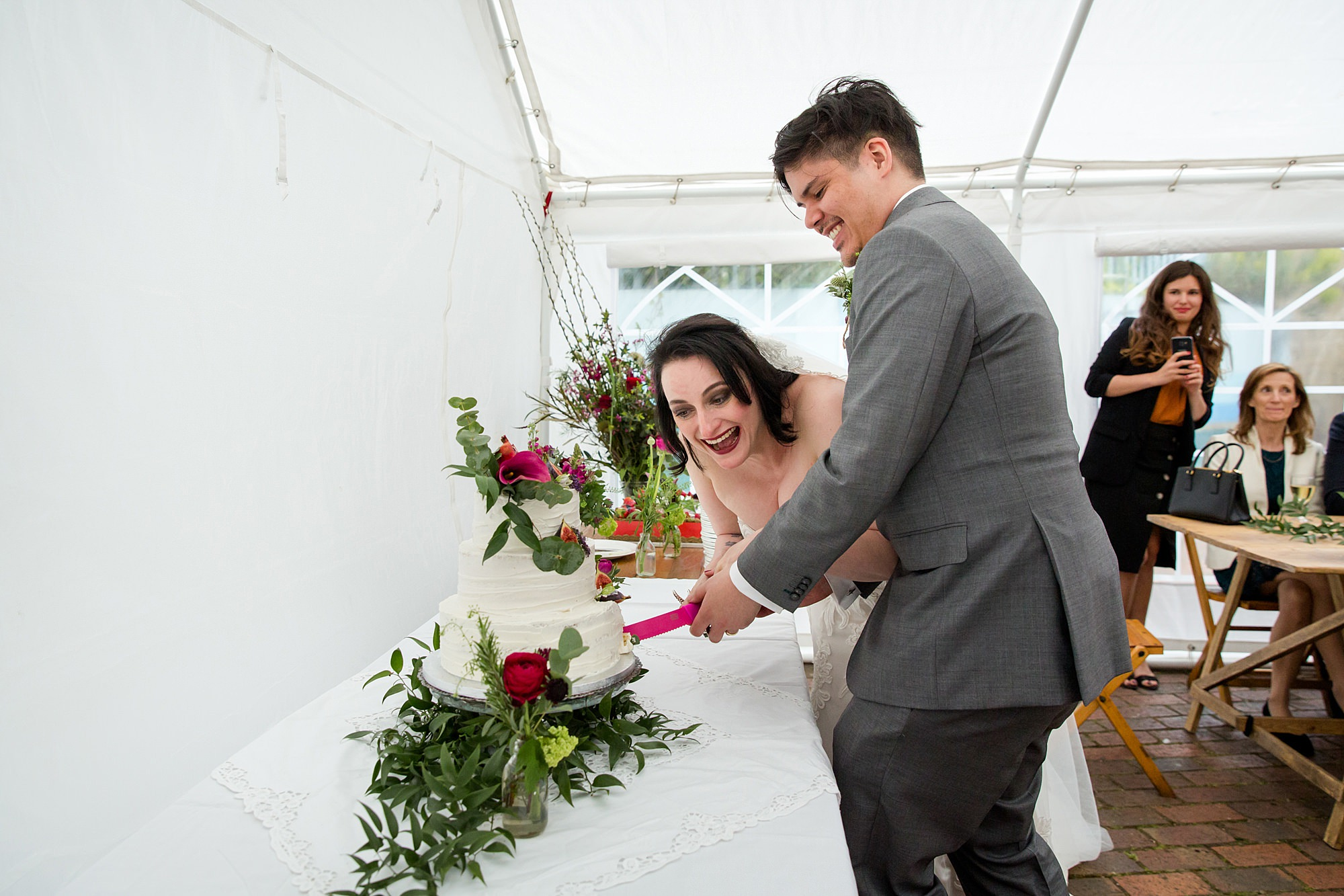 bride and groom laugh as they cut wedding cake
