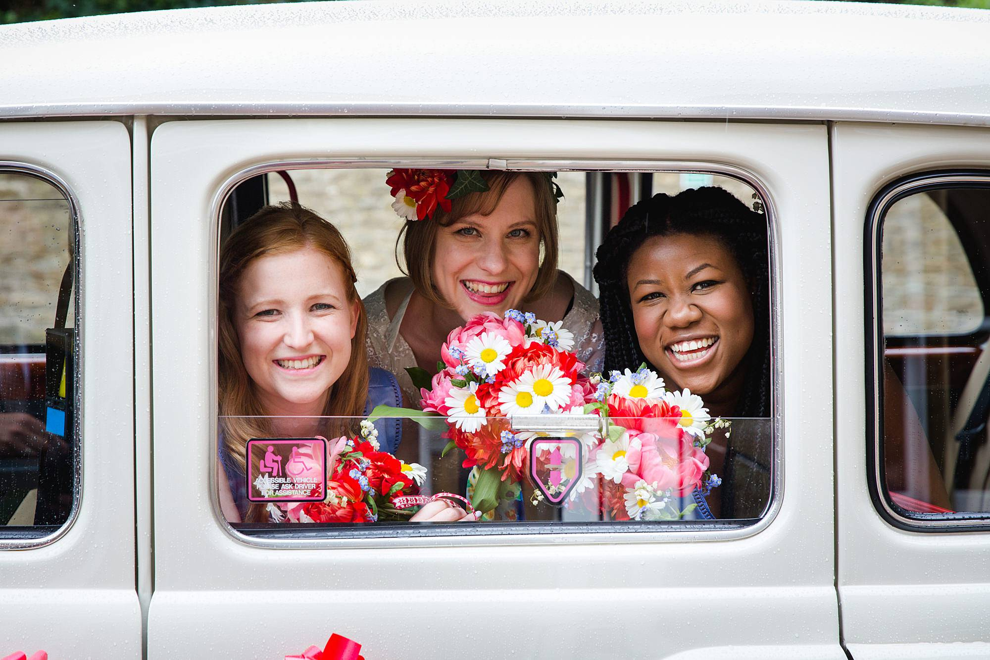bride and bridesmaids smiling through taxicab window