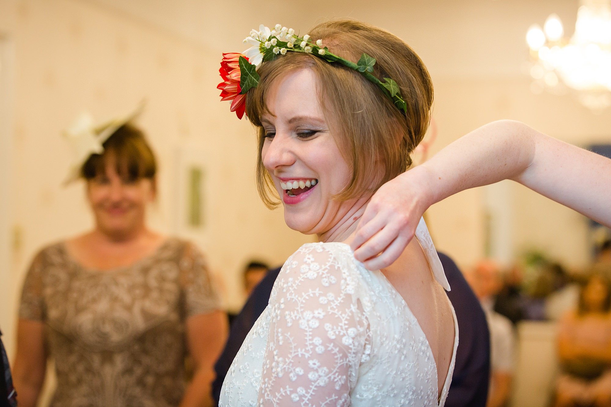 bride laughs as bridesmaid helps her with dress at wedding ceremony in guildford