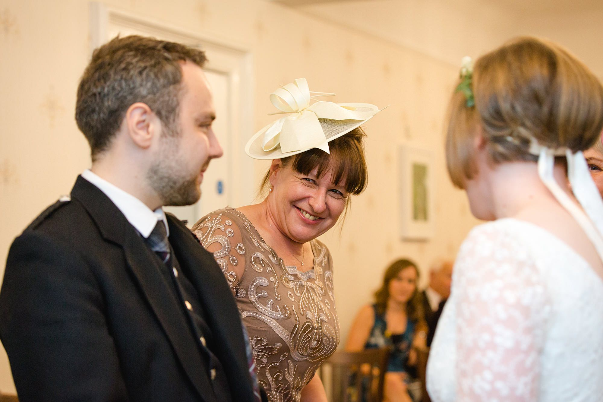 bride's mum smiles at groom during ceremony at guildford register office