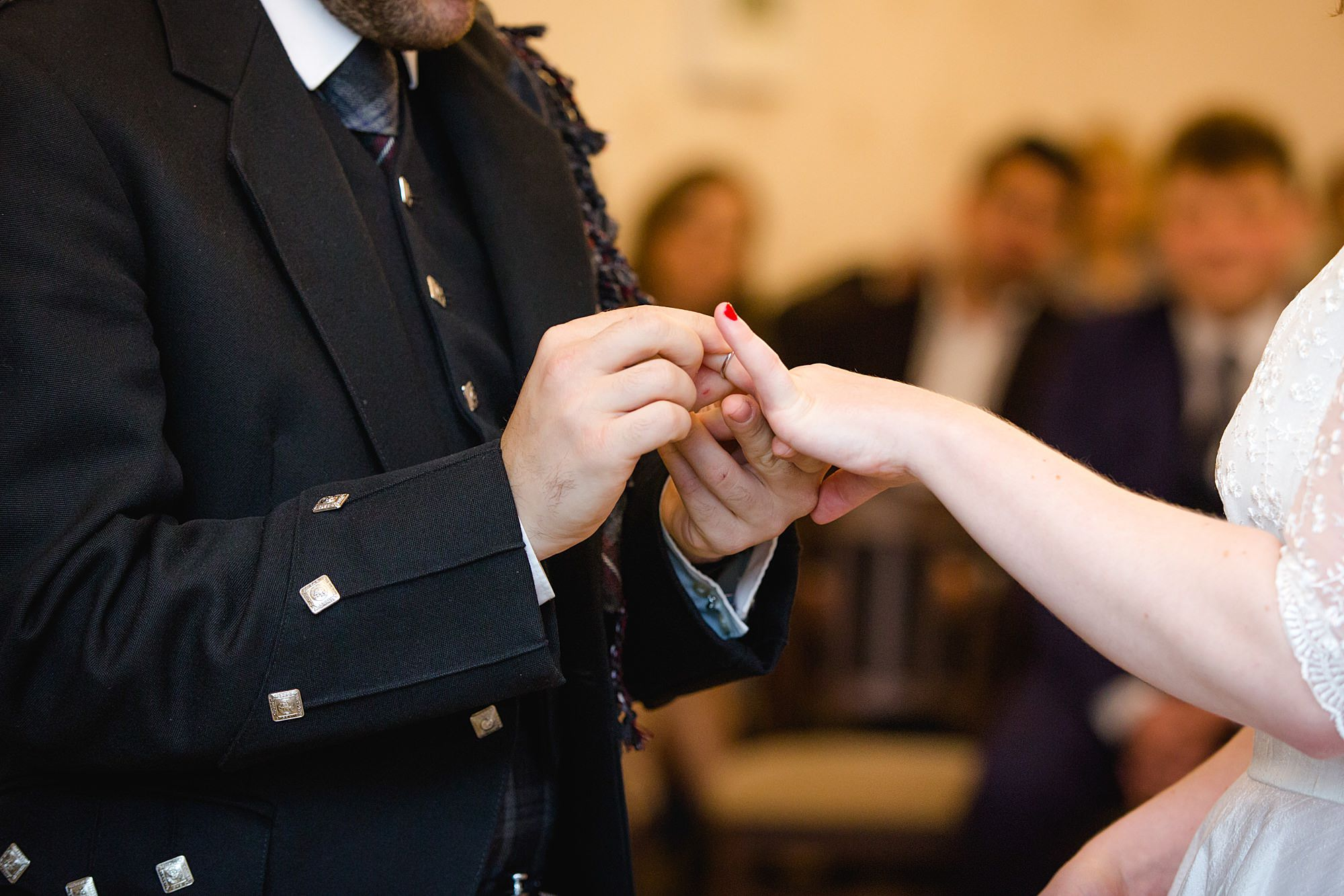 close up of groom putting ring on bride's hands during guildford wedding ceremony