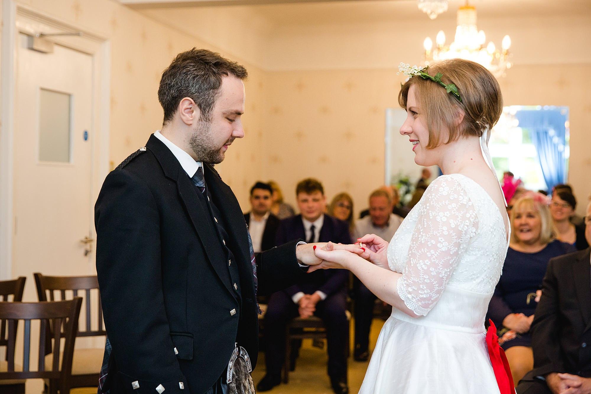 bride and groom exchange rings in guildford wedding