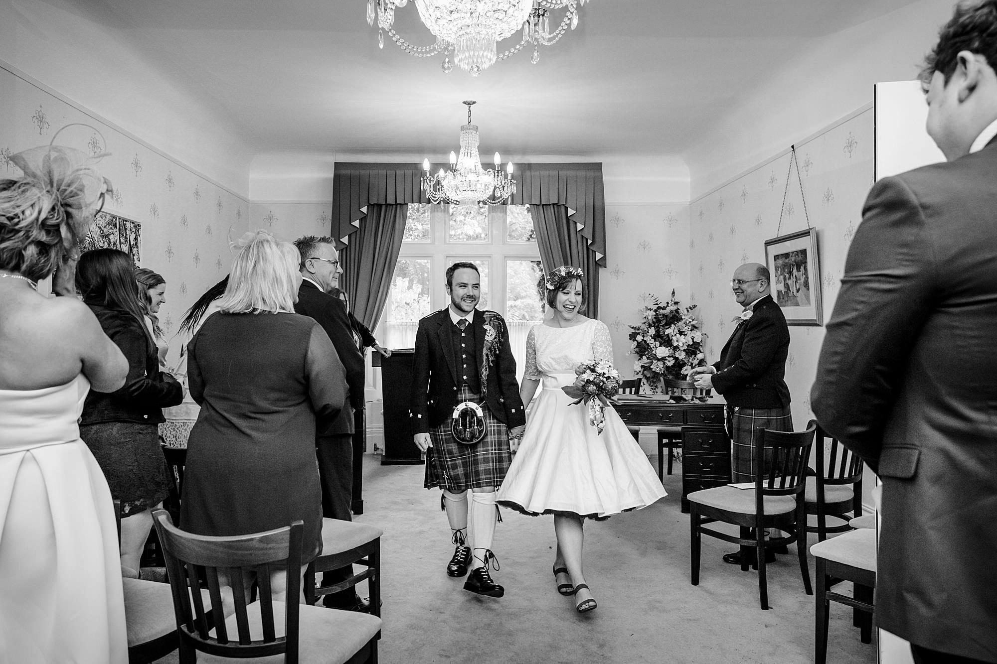 bride and groom walk back down aisle after guildford register office wedding