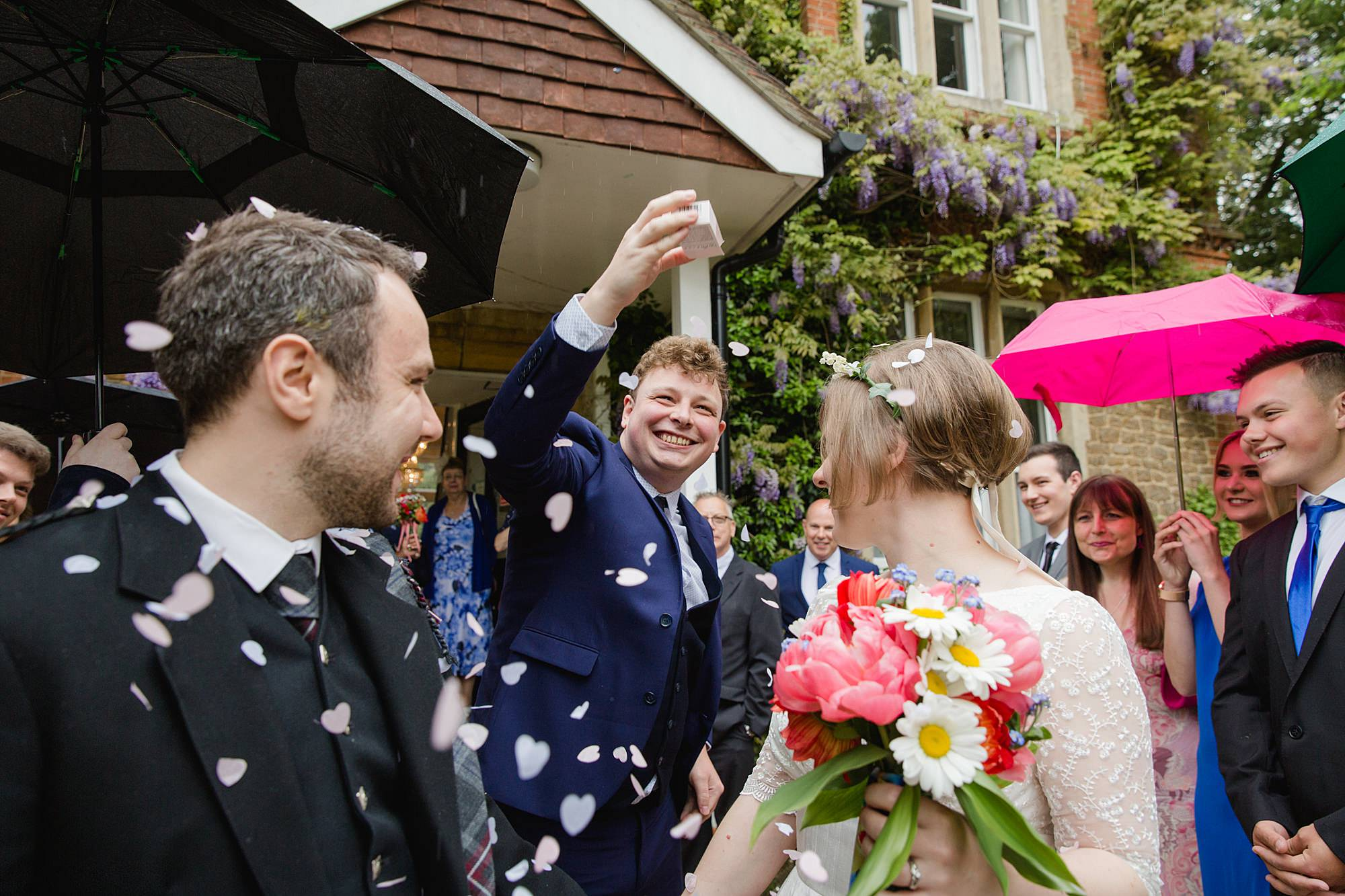 wedding guest dumps confetti on groom and bride after wedding ceremony