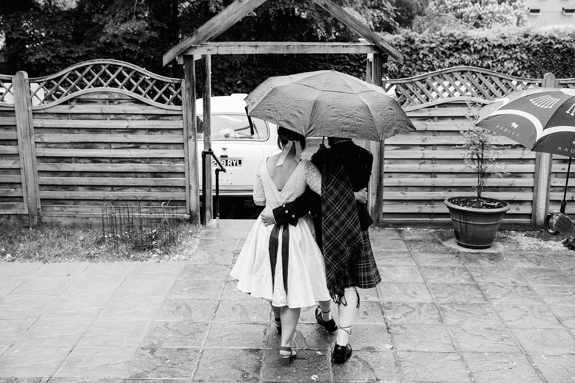 #southlondonwedding #brunelmuesum #brunelmuseumwedding #brunelmesumweddingphotography #outdoorwedding #londonwedding #londonweddingphotographer #funwedding #funweddingphotographer #bohobride #documentarywedding #laidbackwedding #londonpubwedding #londonweddingphotography #southlondonweddingphotography #weddingphotographerlondon #weddingphotographylondon #townhallwedding #weddingmoments #belovedstories #huffpostido #pubweddinglondon #londonweddings #londonweddinginspo #londonweddinginspiration #funnywedding #londonbride #bridelondon #londonweddings #2020wedding bride and groom walking away under an umbrella