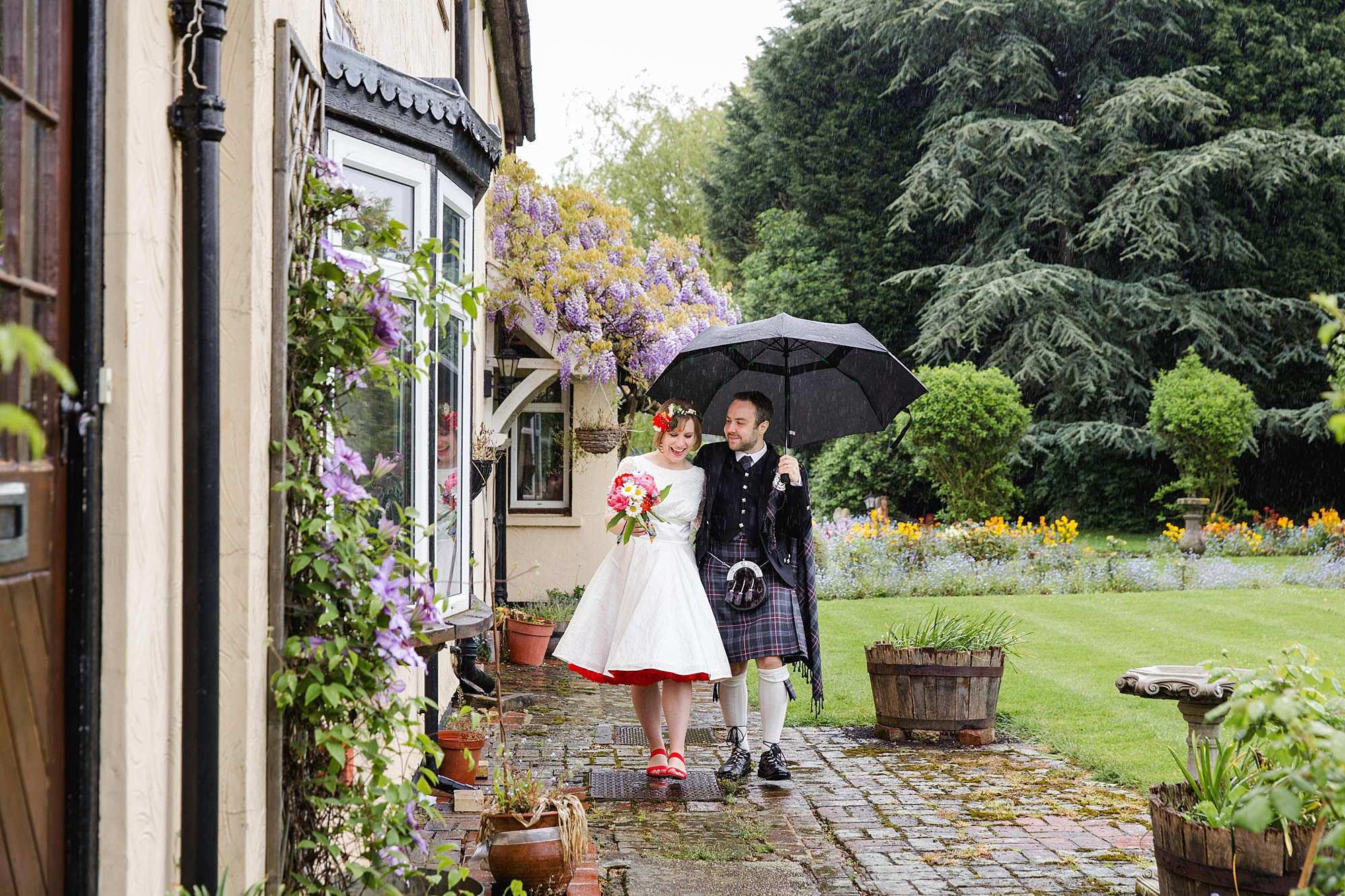 bride and groom smile and walk under umbrellas at norwood farm wedding