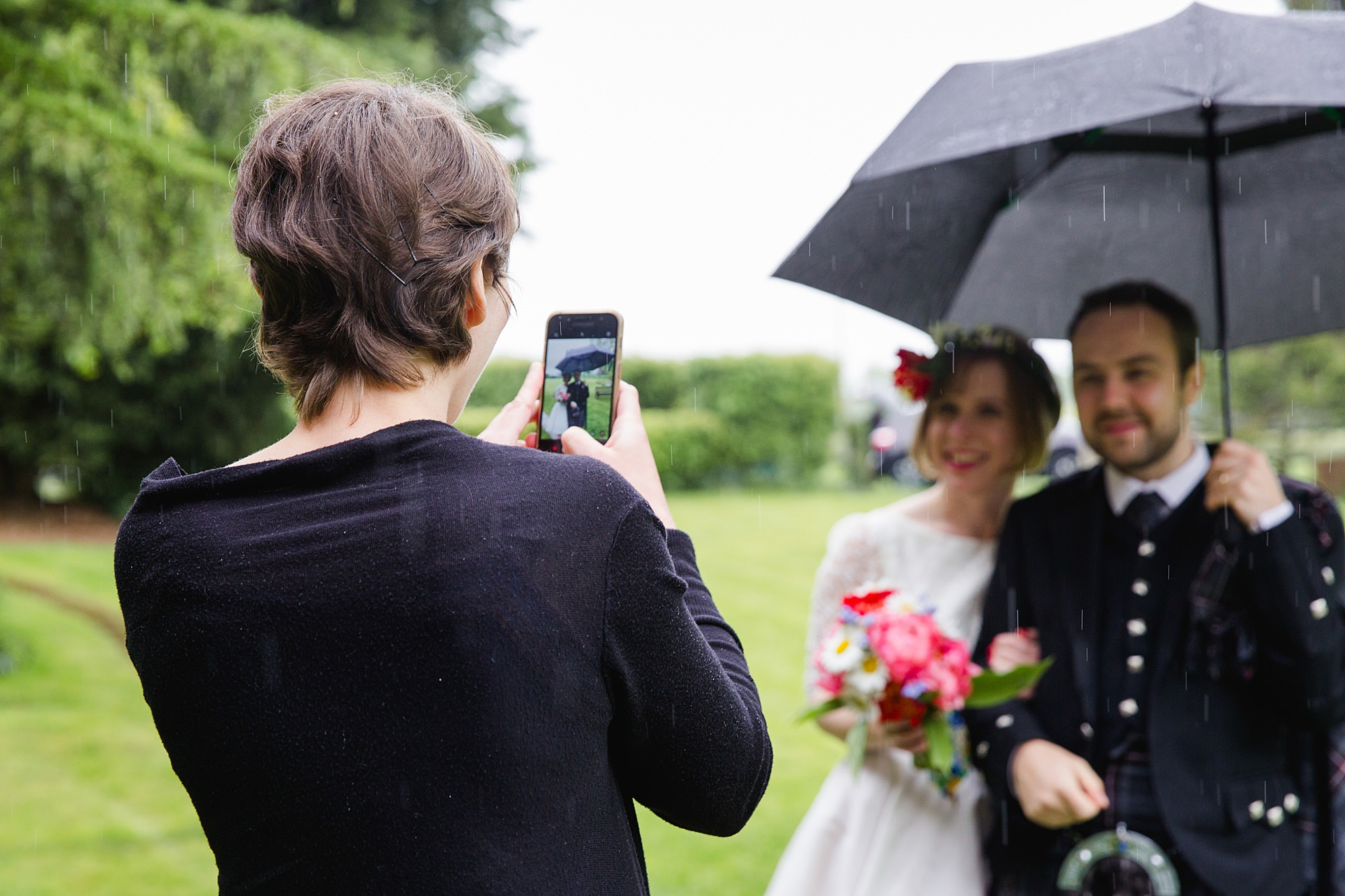 a guest taking picture of bride and groom at norwood farm wedding
