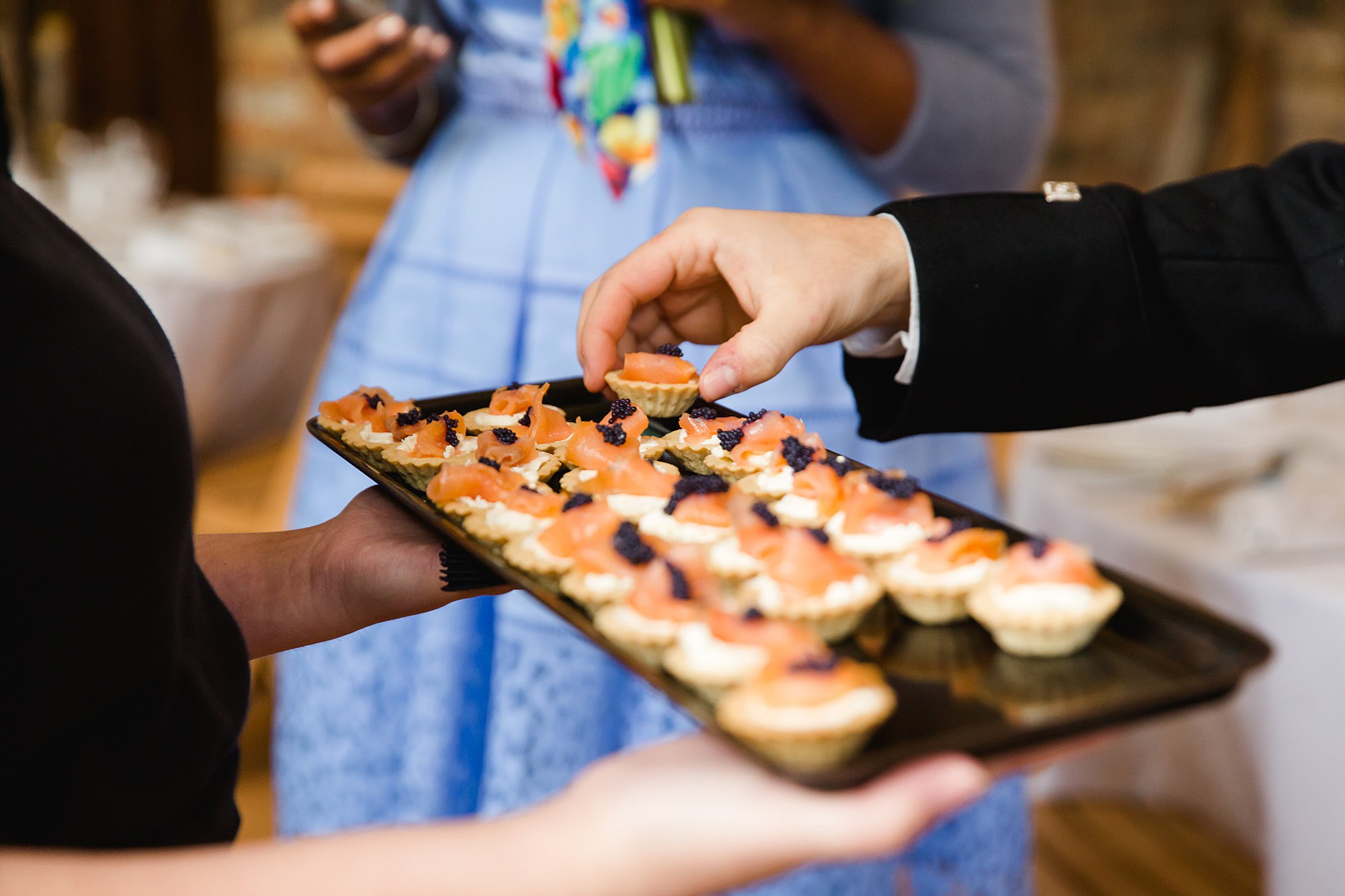 hands reaching for canapés at norwood farm wedding