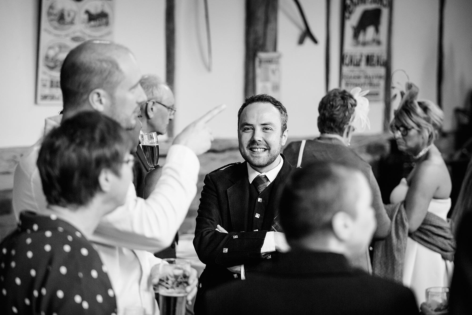 groom laughs with his guests at norwood farm wedding