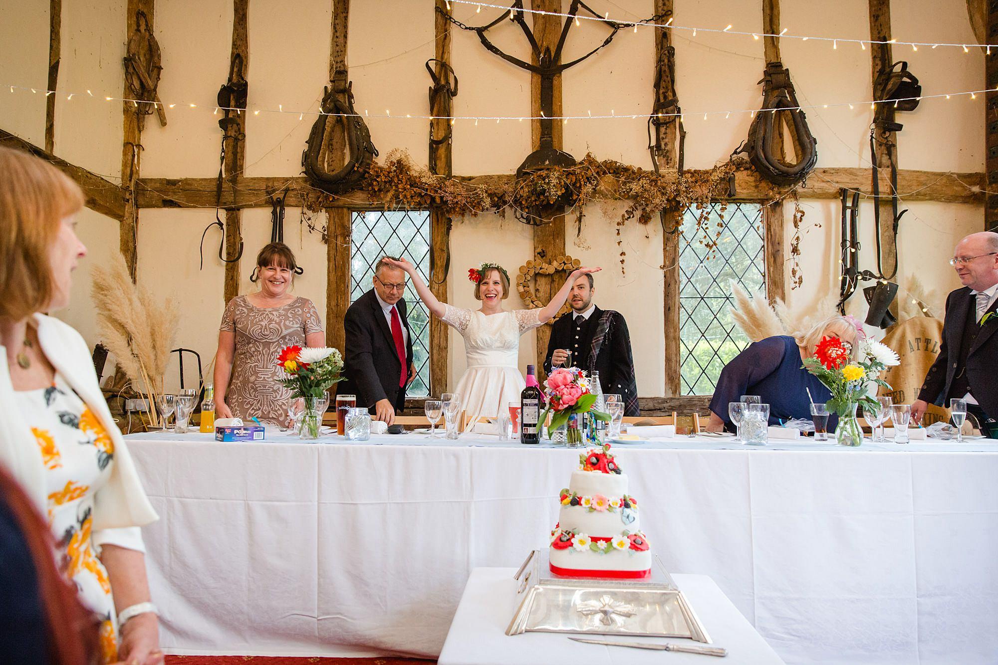 bride cheering at top table at Fun DIY wedding