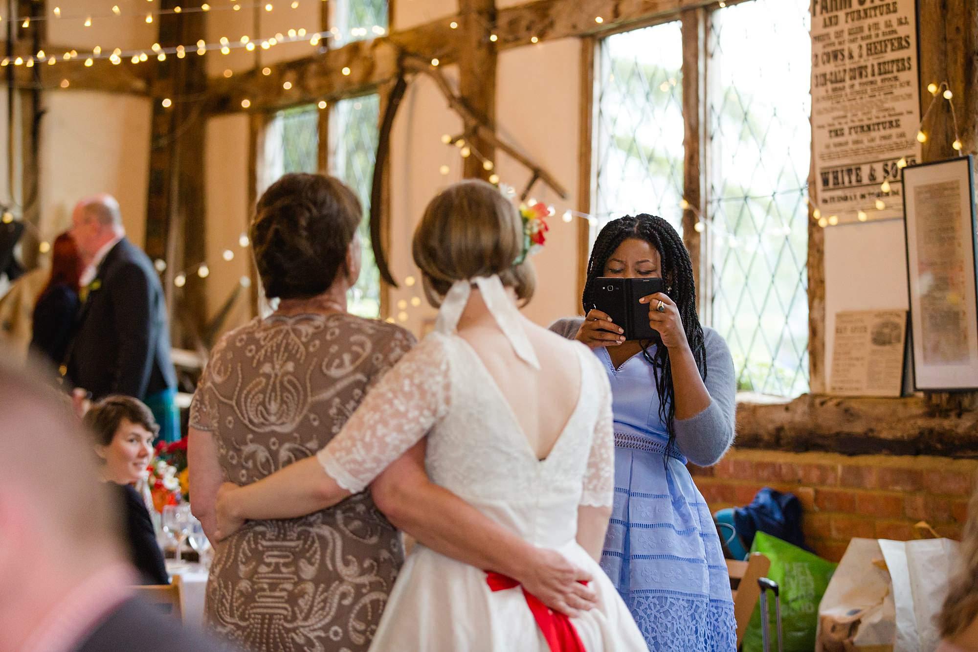 bridesmaid takes picture of bride