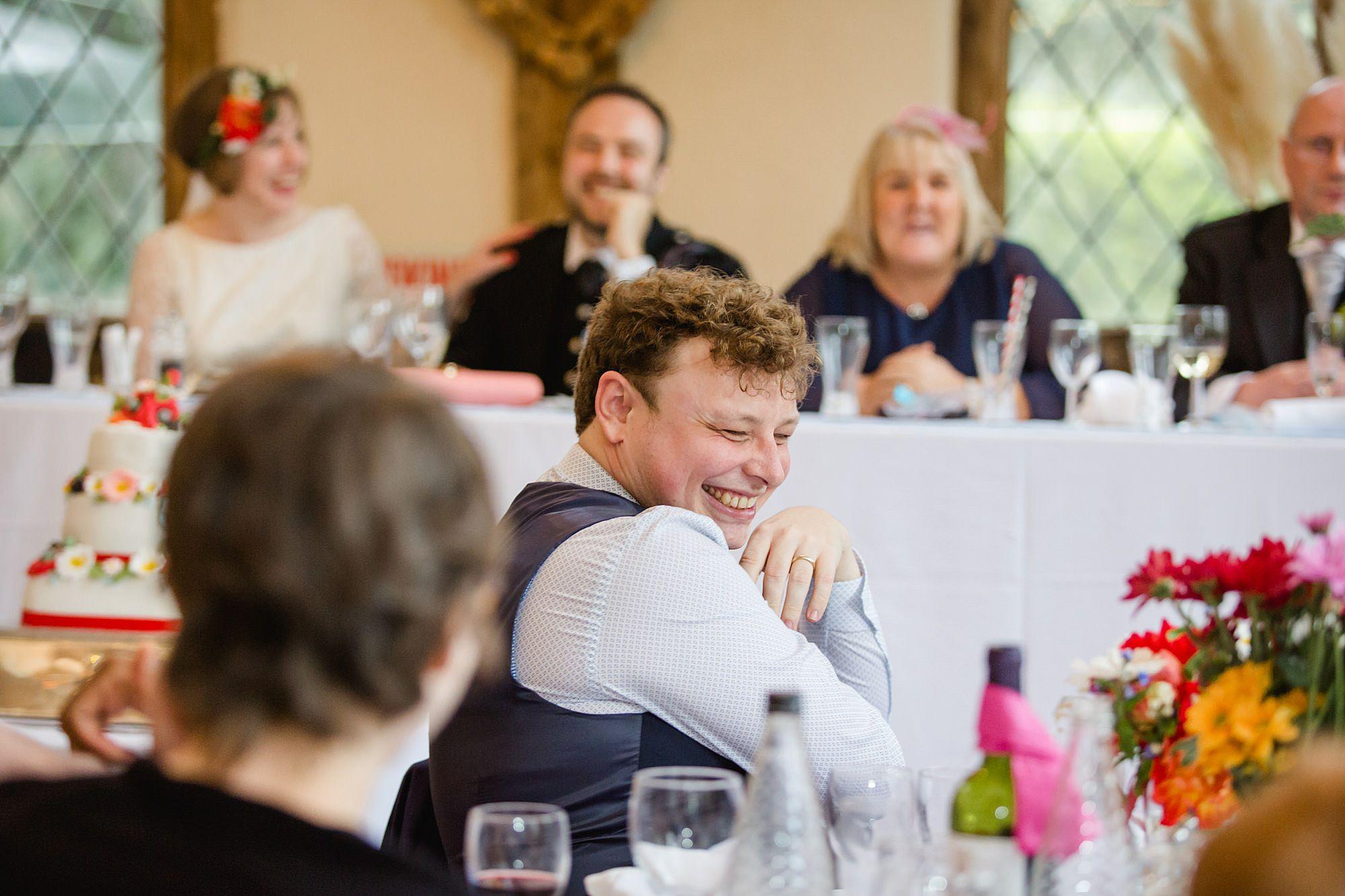 Fun DIY wedding guest laughing during speeches