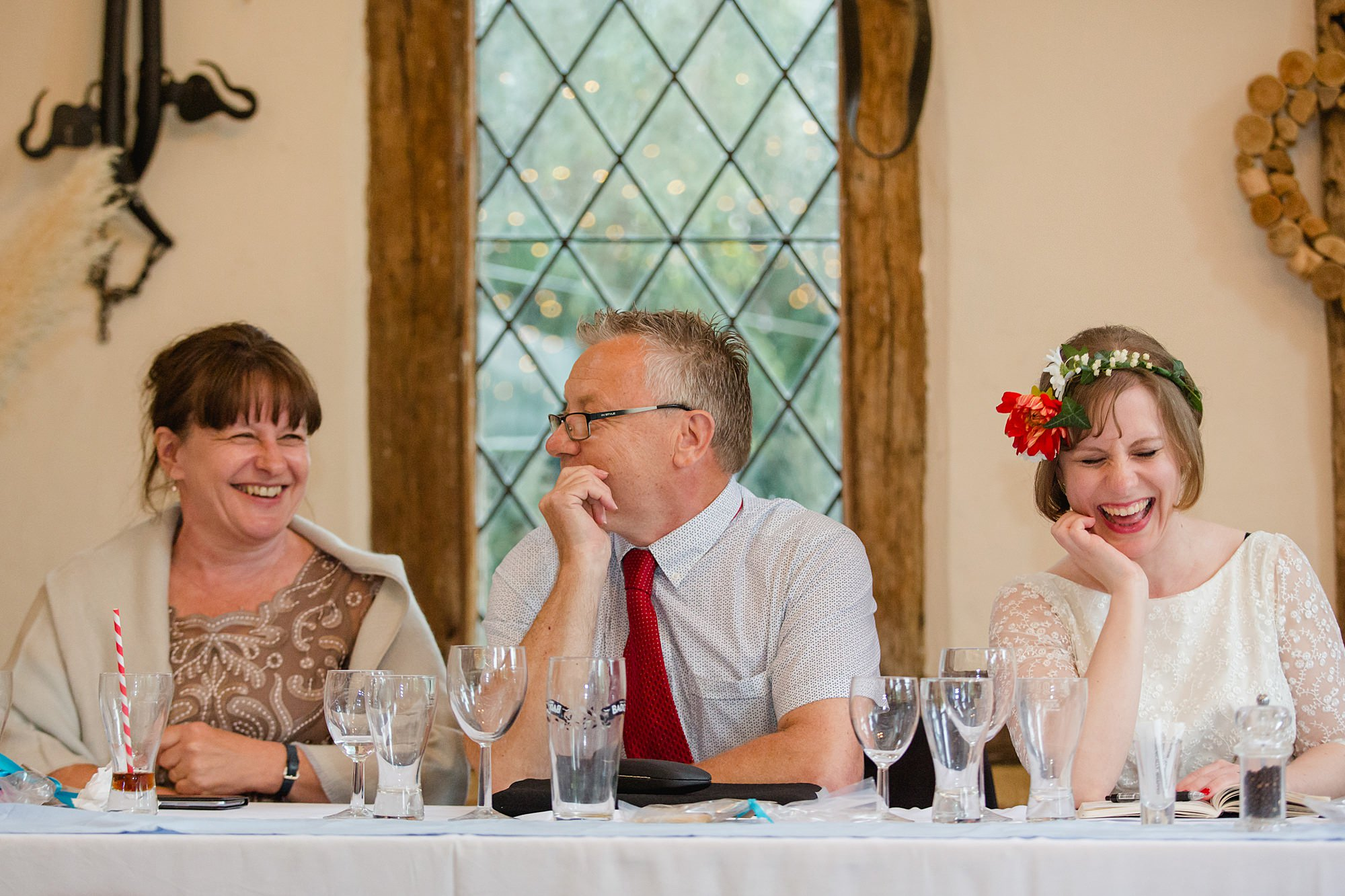 bride and family laughing at groom's speech at Fun DIY wedding
