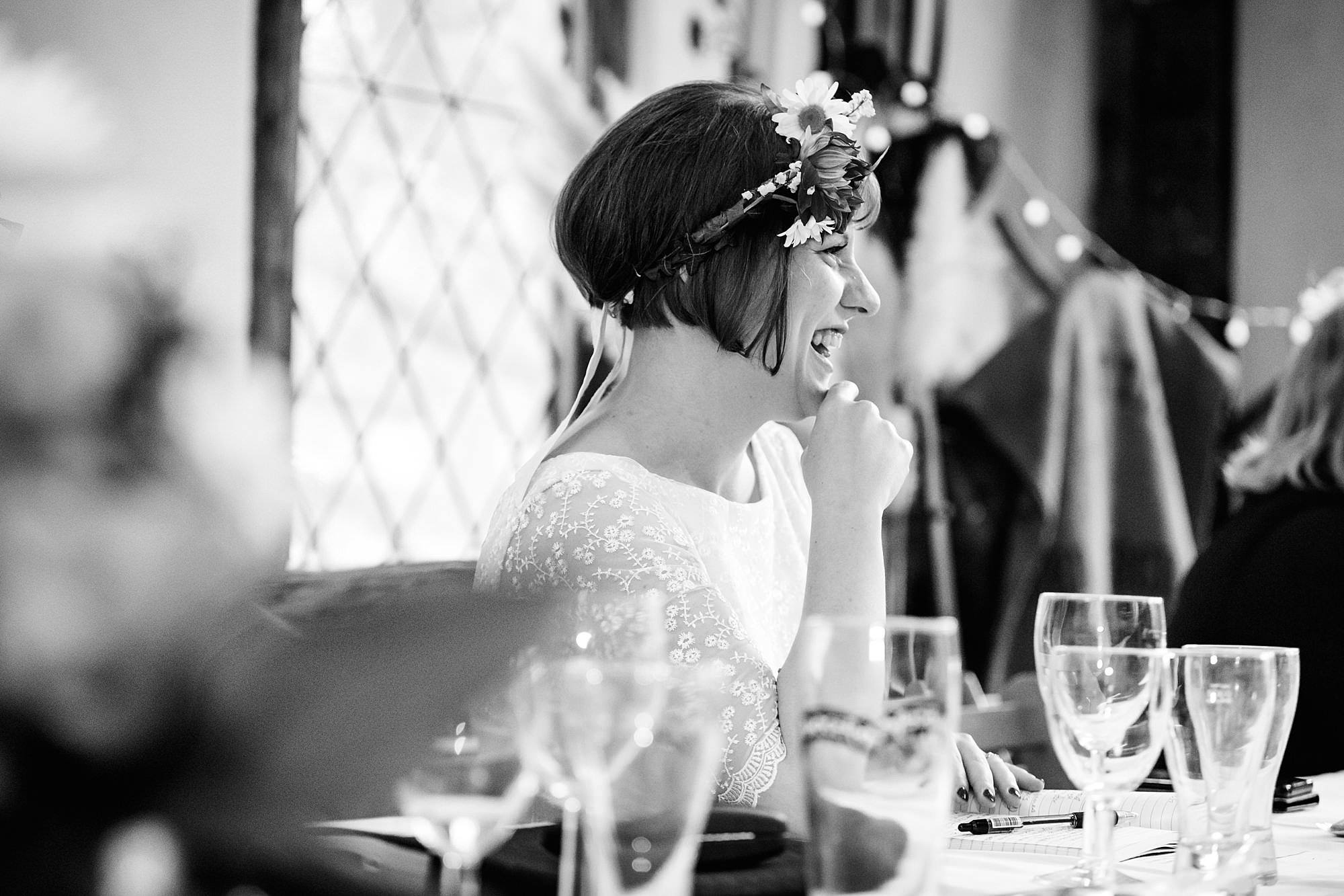 a bride laughs at groom's speech at norwood farm wedding