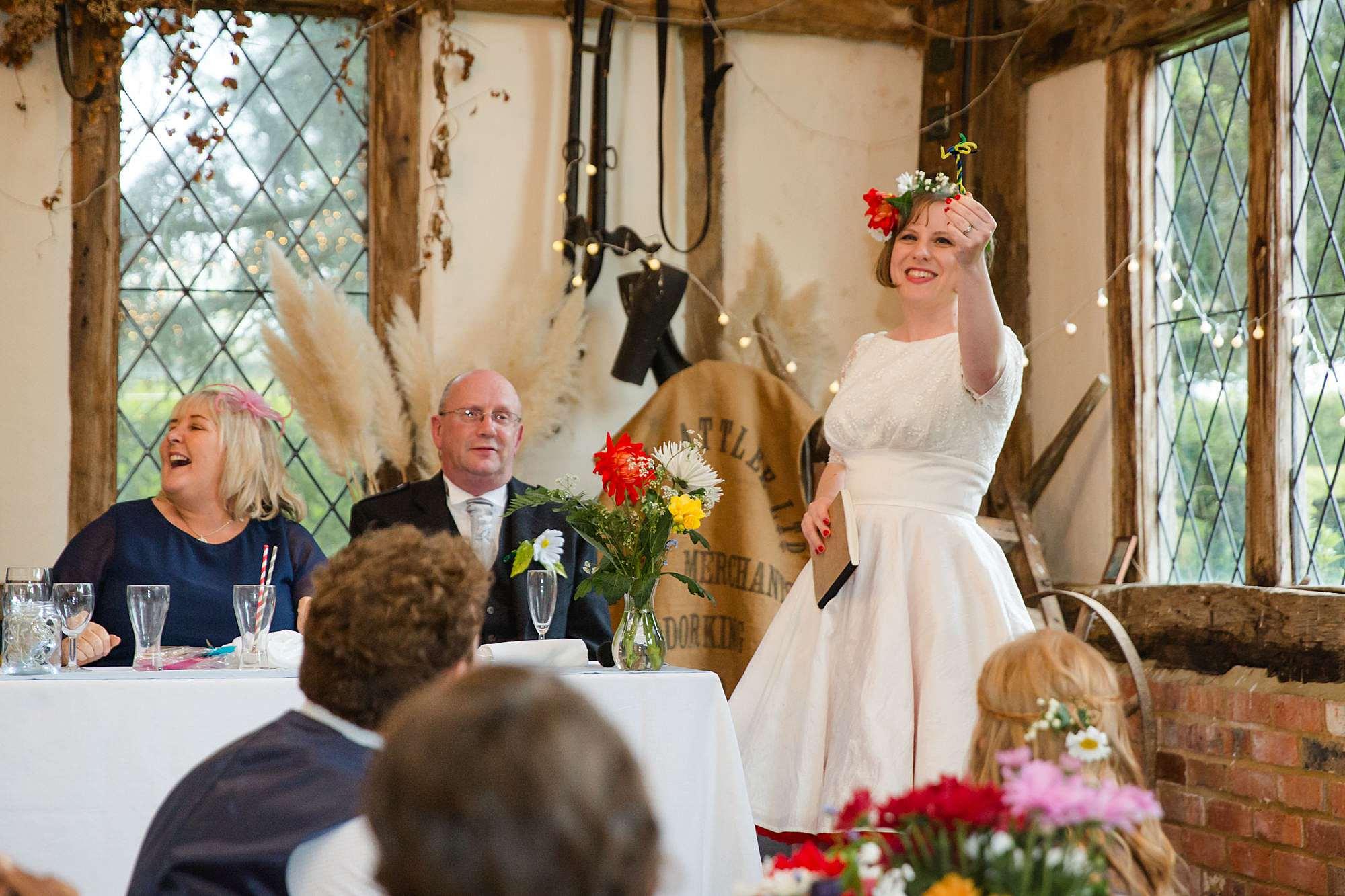 bride holds up handmade flower