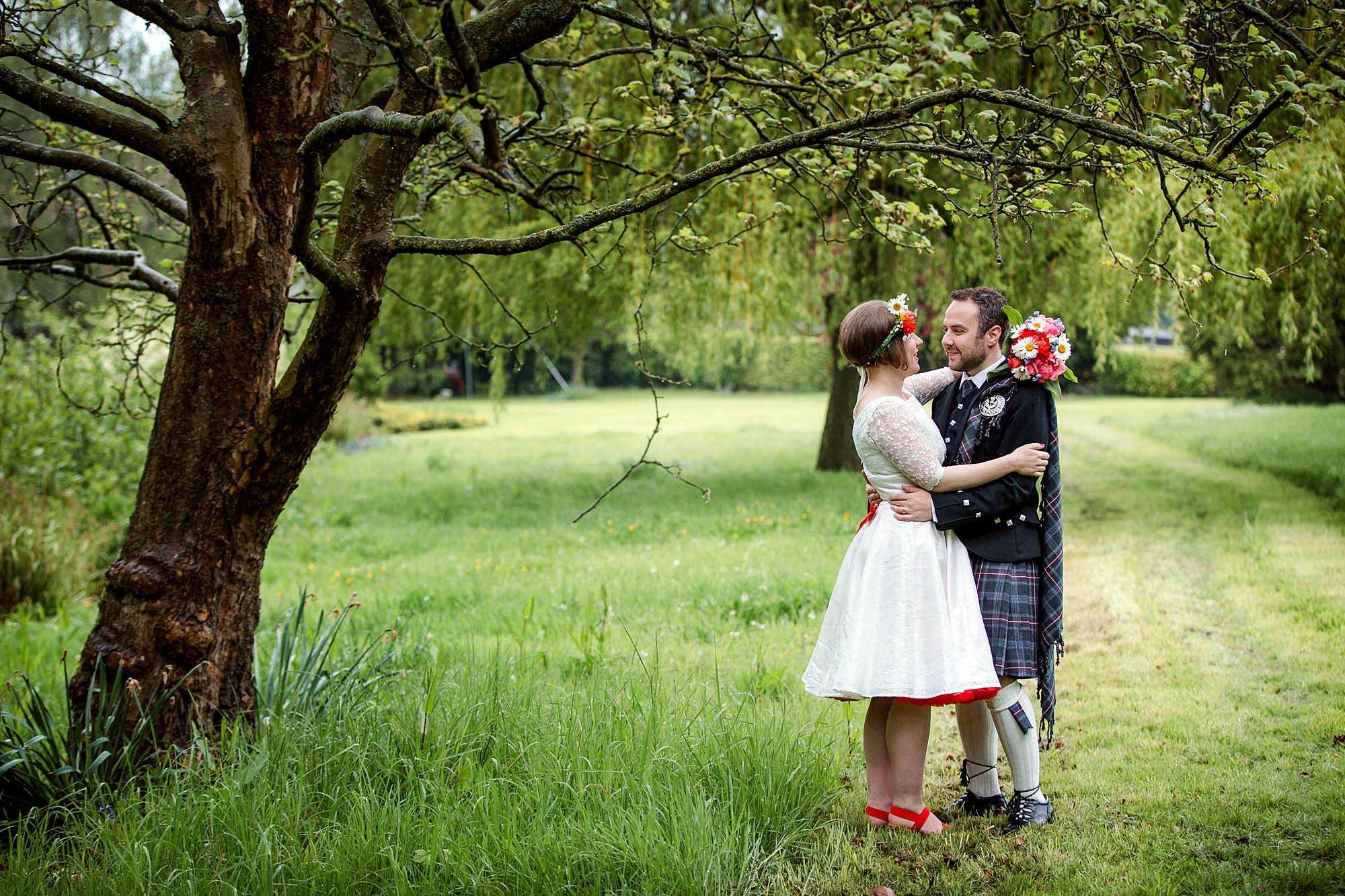 bride and groom hug in green gardens of norwood farm
