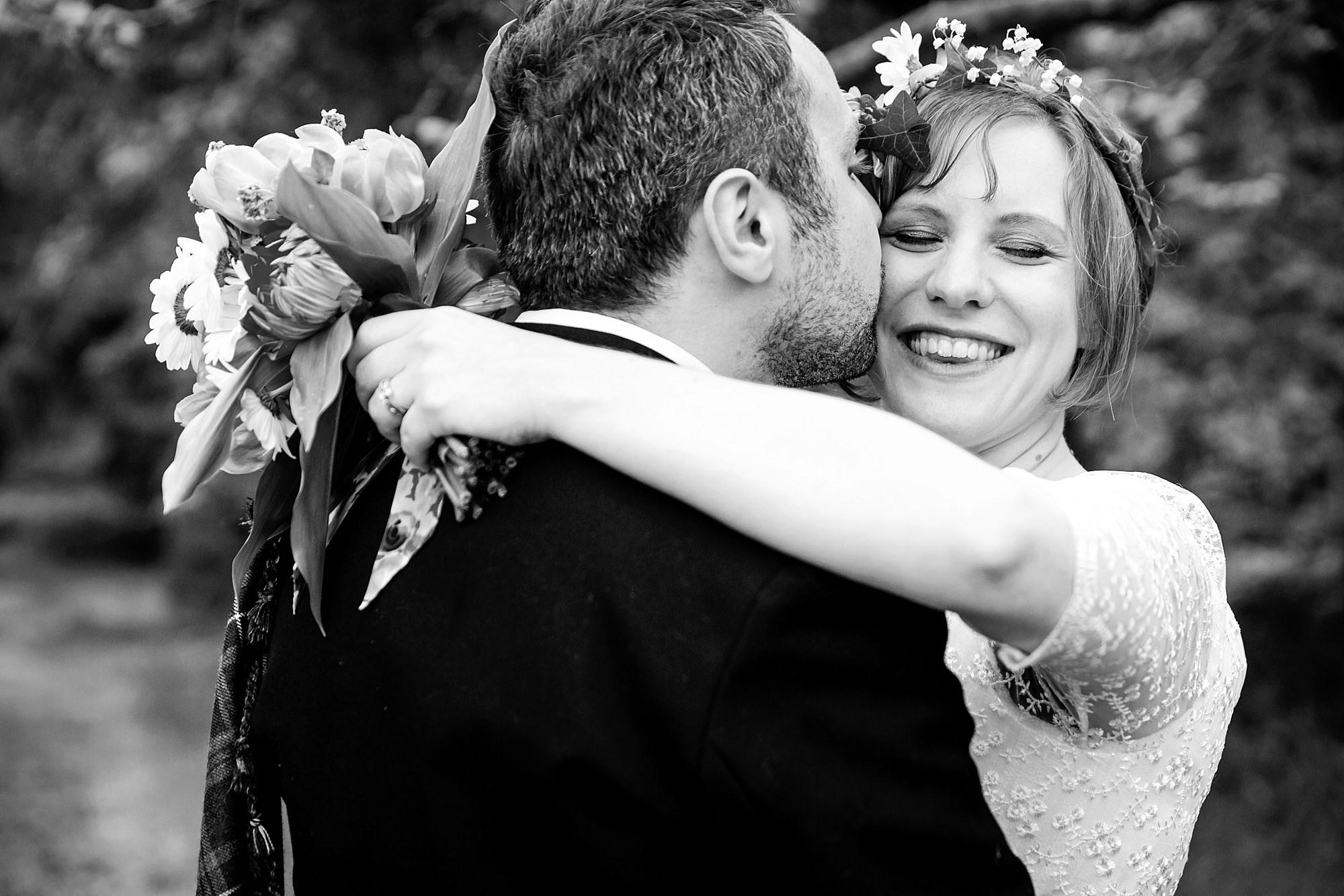 groom kissing bride on cheeks at Fun DIY wedding