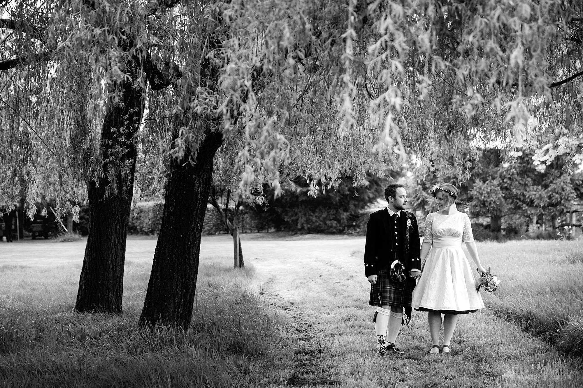 bride and groom under willow tree at norwood farm