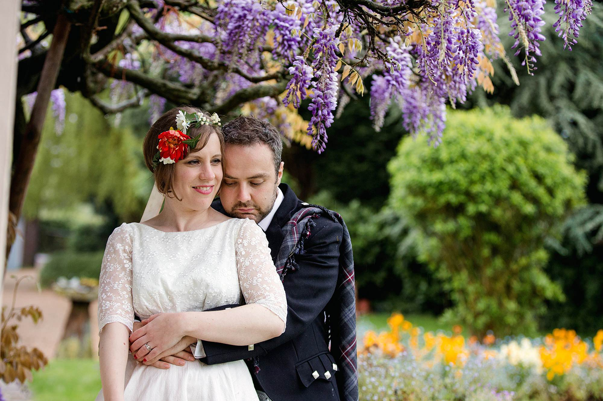 bride and groom with wisteria flowers at norwood farm