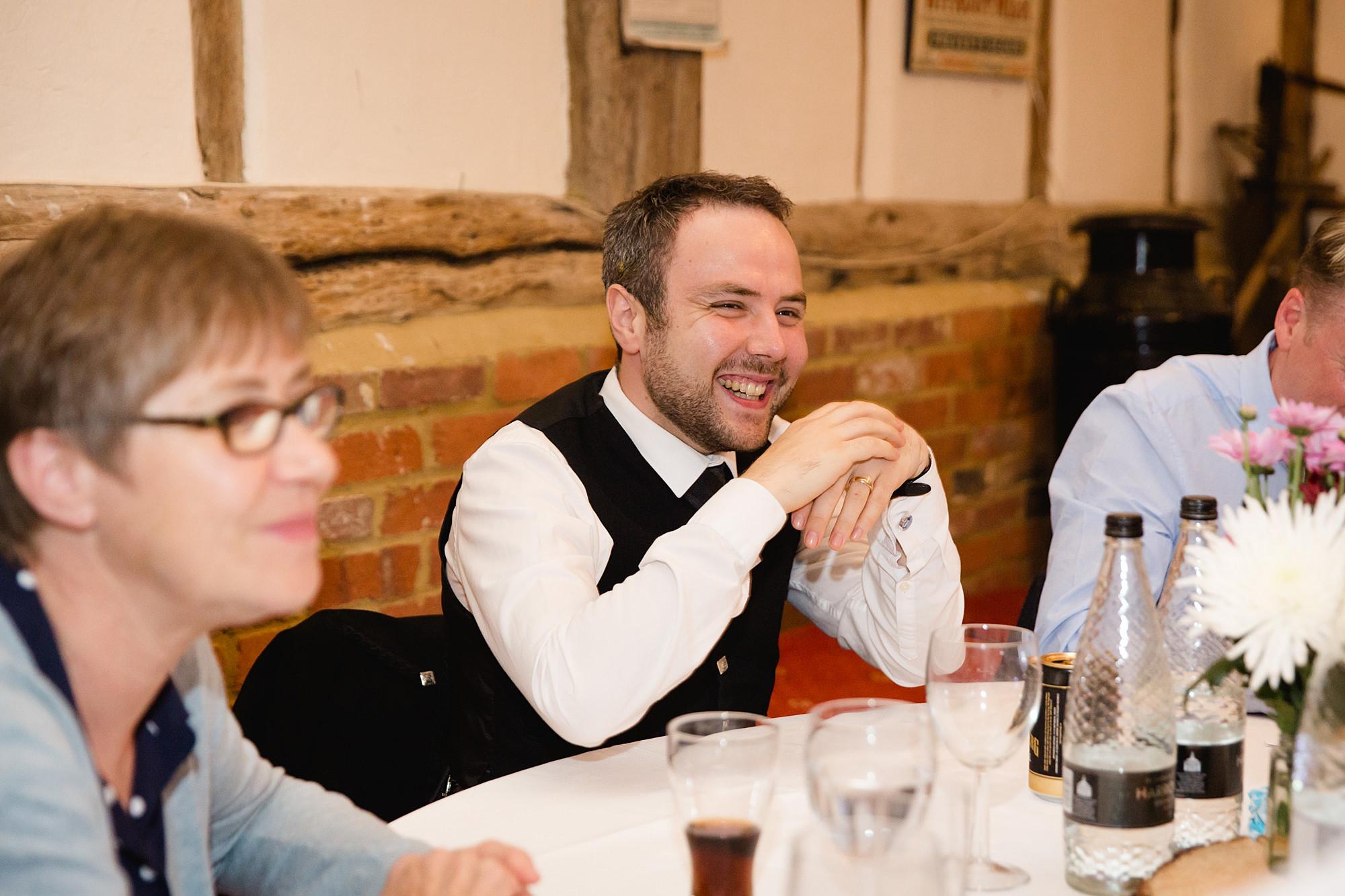 groom laughs during wedding quiz