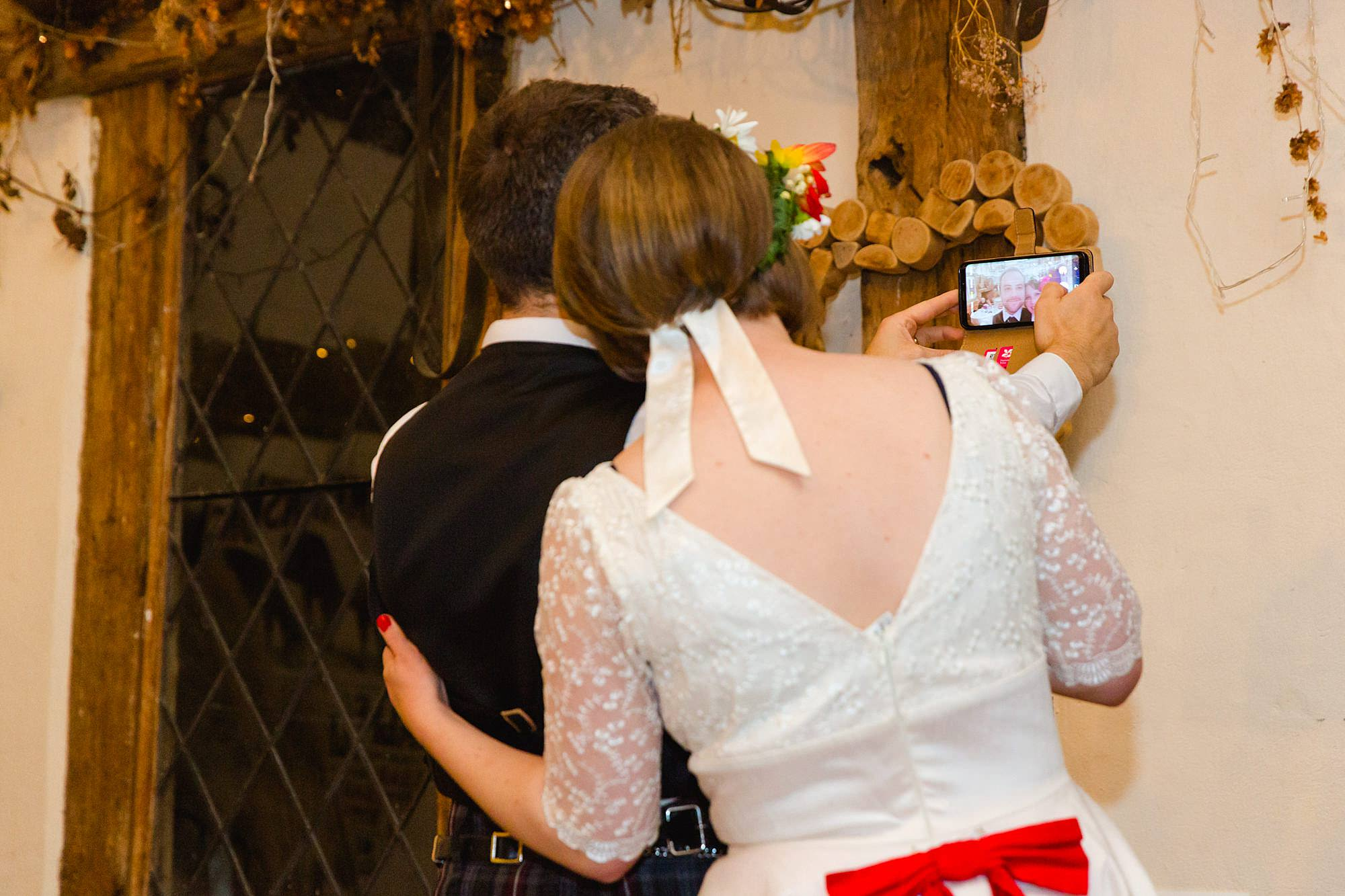 bride and groom take a selfie together at their wedding
