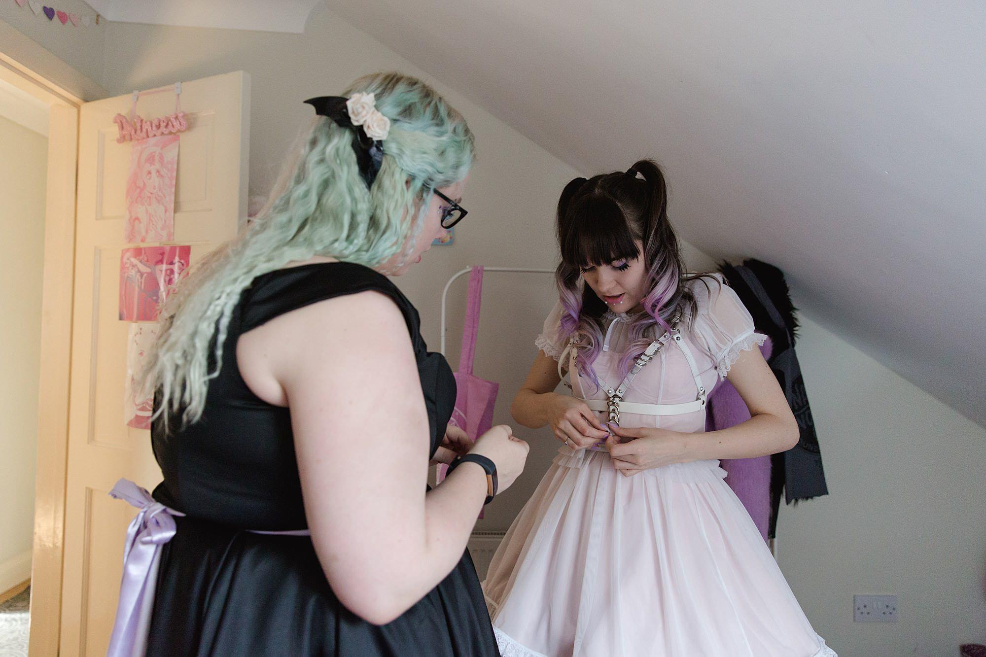 bridesmaid helps bride tie her wedding dress belt harness