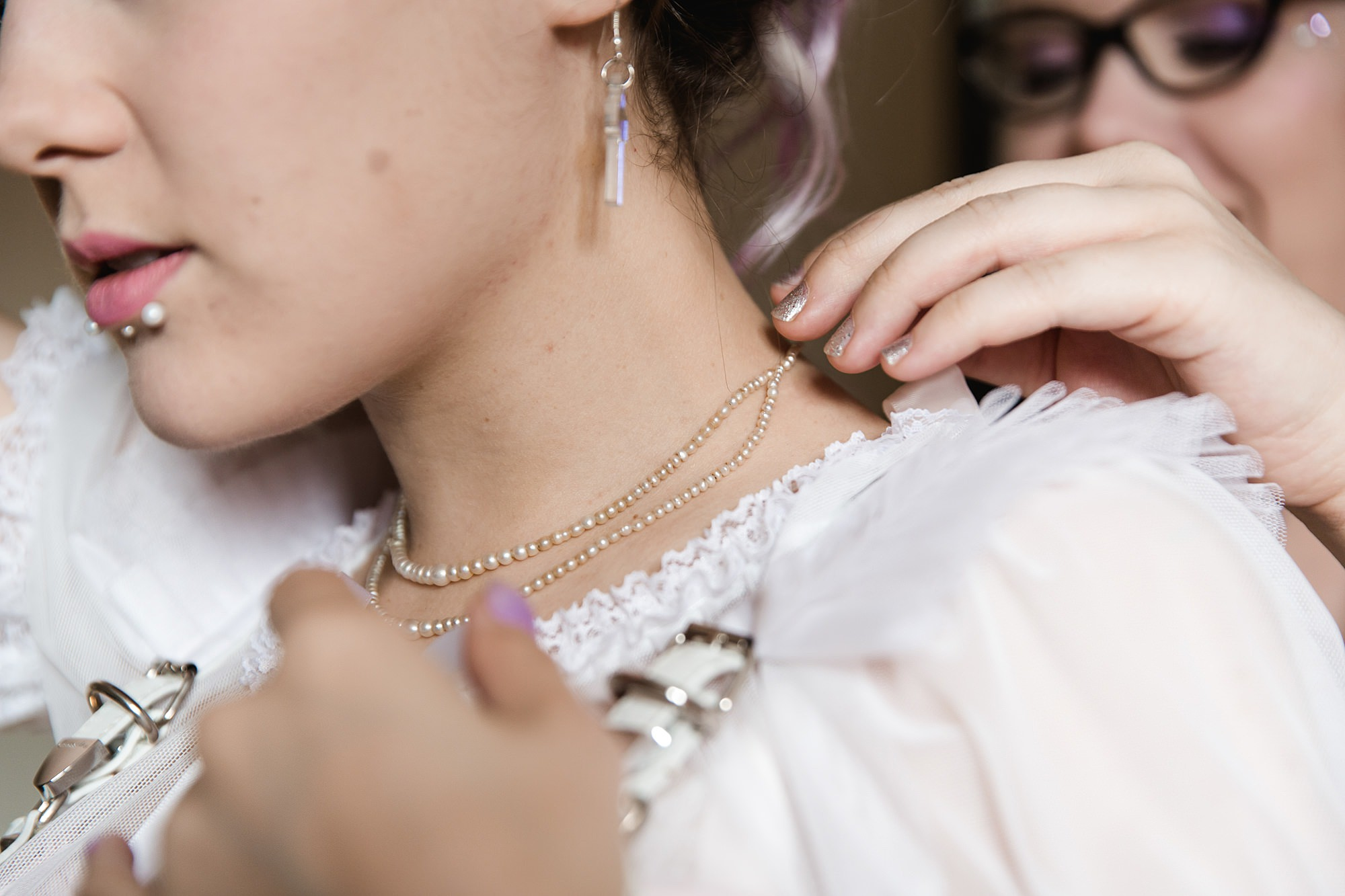 a bride puts on pearl necklace ahead of Gothic wedding London