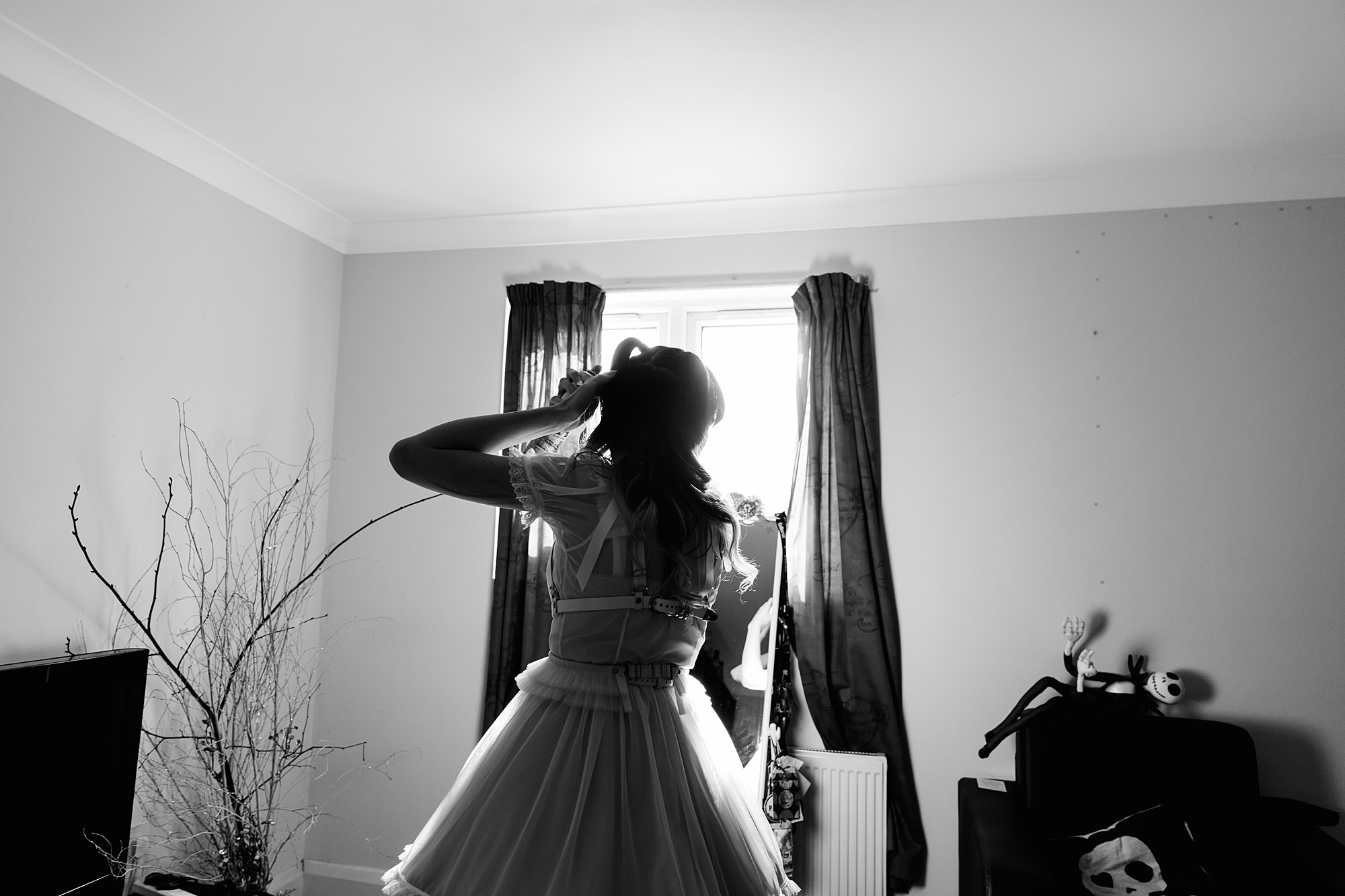 bride spraying hairspray in front of mirror