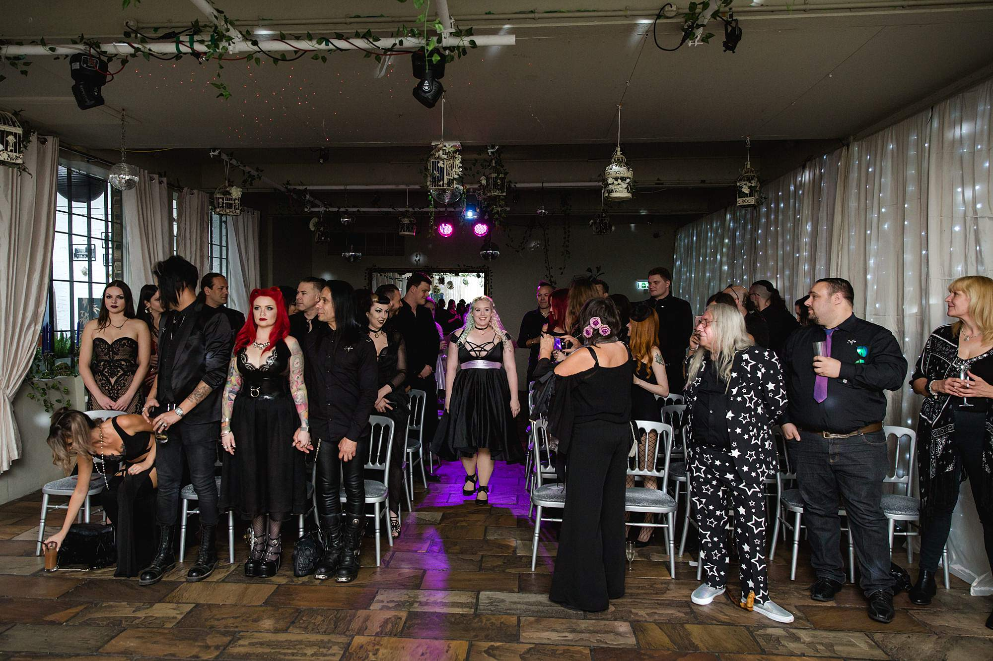 bridesmaid walks down the aisle for gothic wedding at islington metalworks