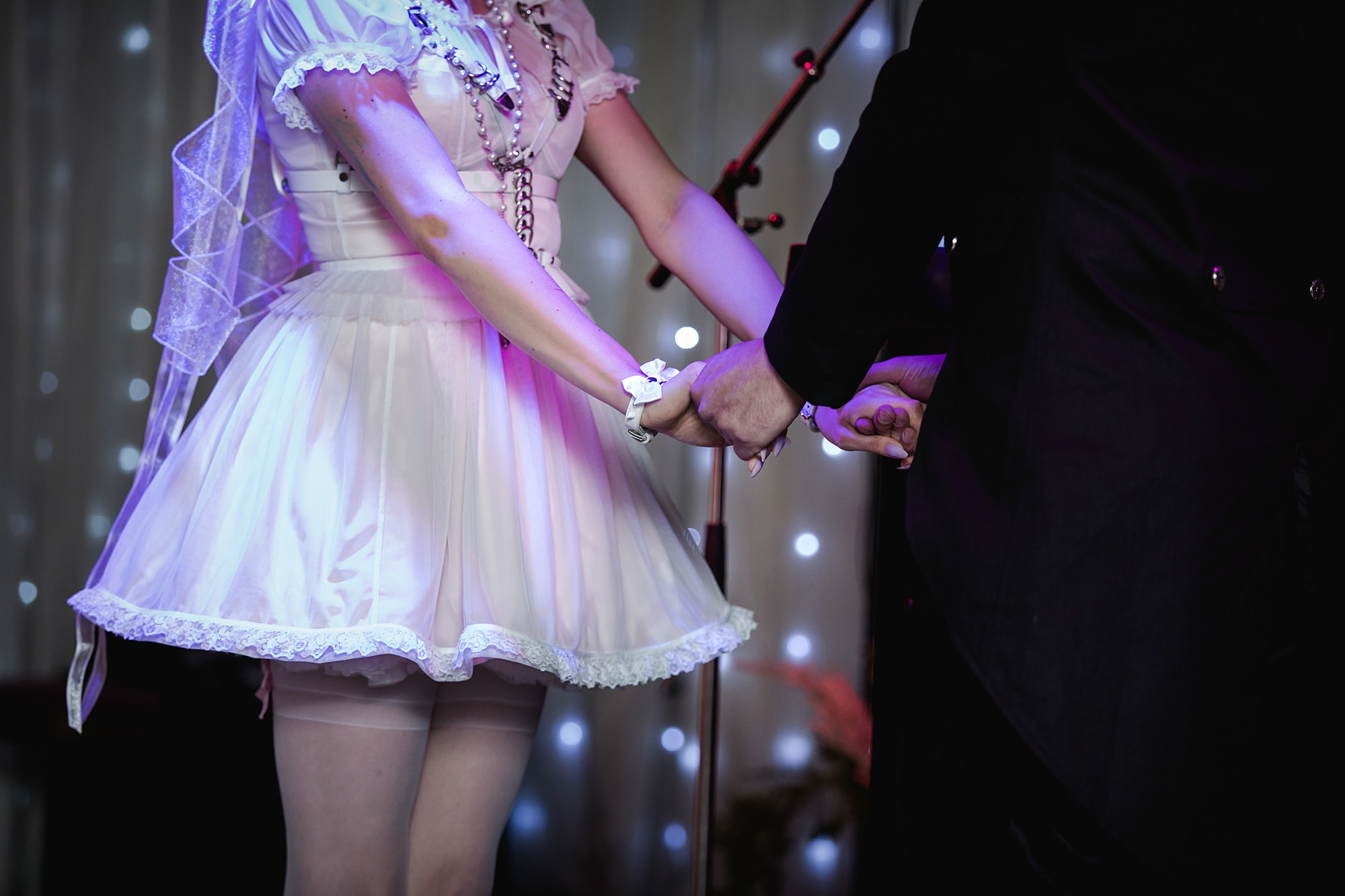 close up of goth bride and groom holding hands