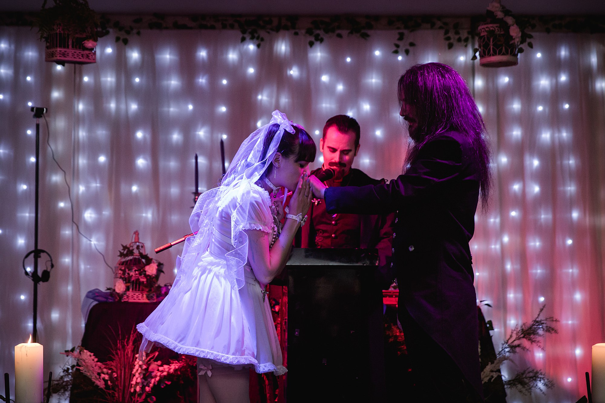 bride kisses groom's hand at altar during goth wedding at islington metalworks